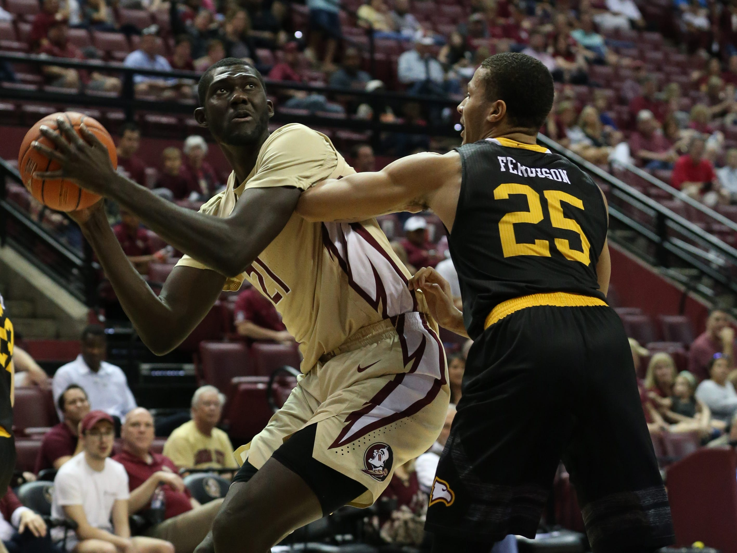 Florida State Seminoles center Christ Koumadje (21) looks over Winthrop Eagles forward Josh Ferguson (25) towards the hoop. The Florida State Seminoles host the Winthrop Eagles for men's basketball at the Tucker Civic Center, Tuesday, Jan. 1, 2019.