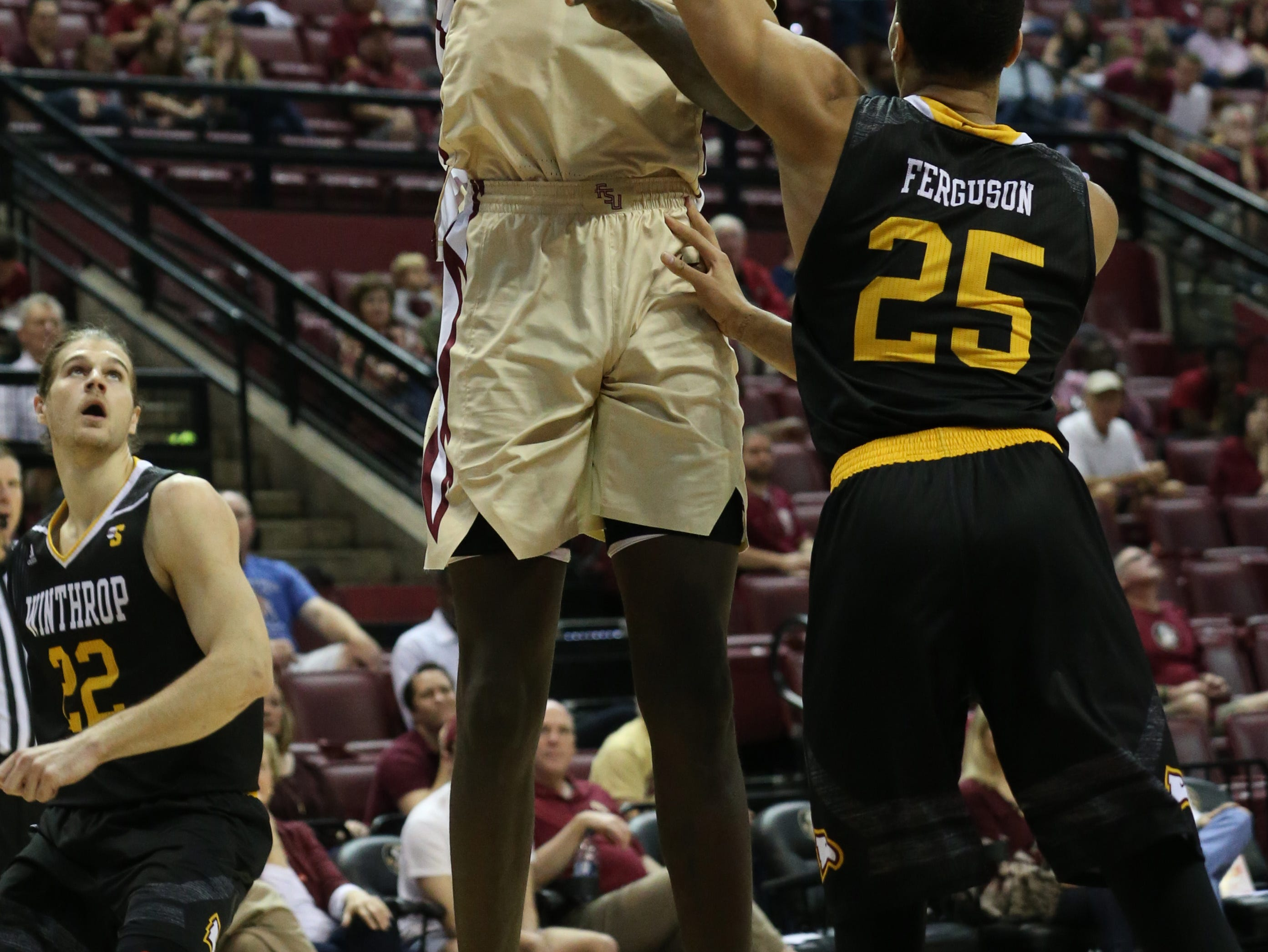 Florida State Seminoles center Christ Koumadje (21) shoots over Winthrop Eagles forward Josh Ferguson (25) from inside the paint. The Florida State Seminoles host the Winthrop Eagles for men's basketball at the Tucker Civic Center, Tuesday, Jan. 1, 2019.