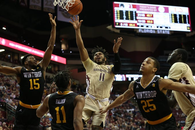Florida State Seminoles guard David Nichols (11) shoots over Winthrop Eagles guard Charles Falden (11) and Winthrop Eagles forward Jermaine Ukaegbu (15) from inside the paint. The Florida State Seminoles host the Winthrop Eagles for men's basketball at the Tucker Civic Center, Tuesday, Jan. 1, 2019.