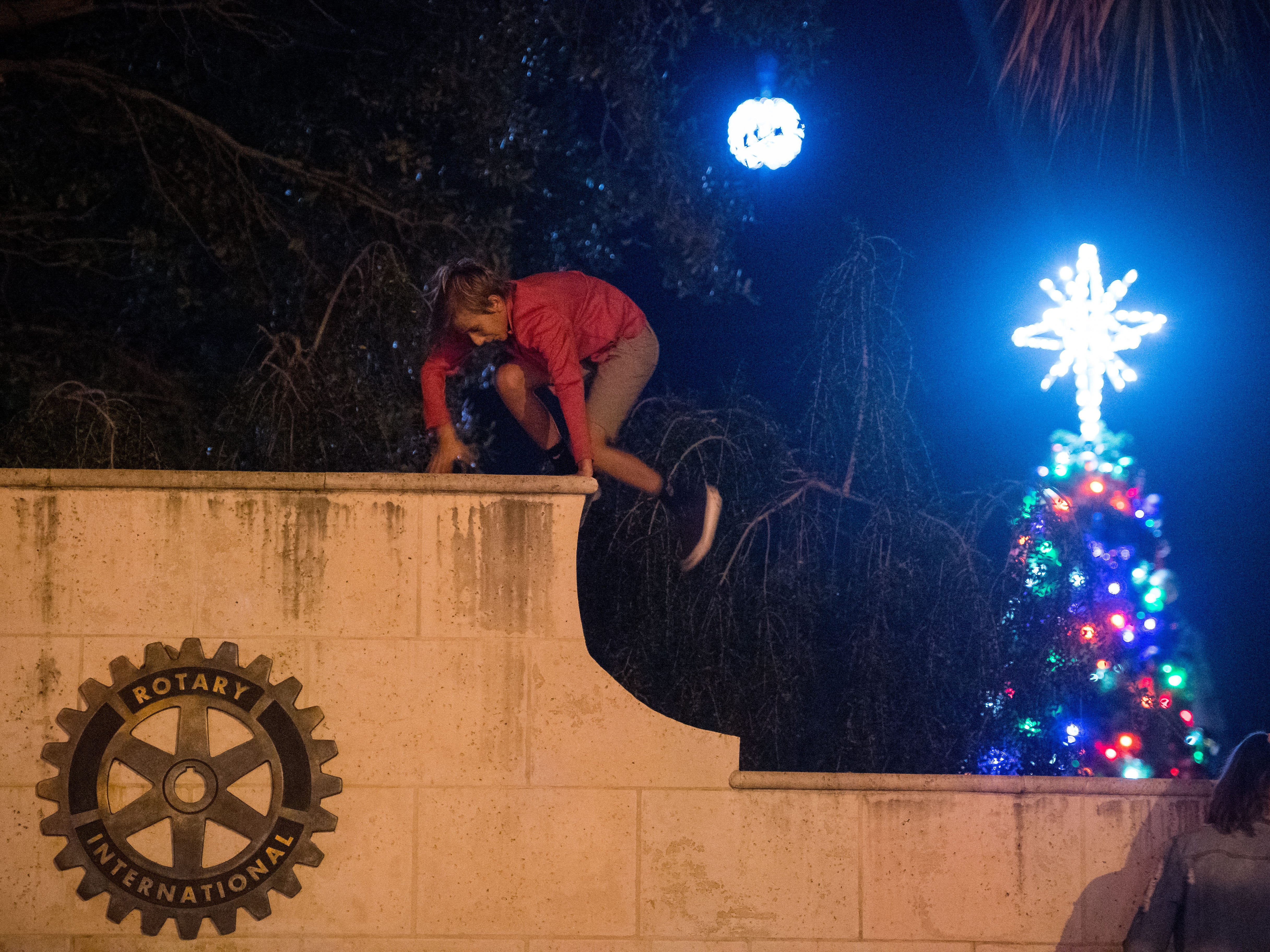 "Wyatt Burdick, 10, of Vero Beach, climbs outside The Heritage Center, as the New Year's ball and Christmas tree can be seen behind him, ahead of the Heritage Center's New Year's Eve ""Party of the Century — Diamonds Are Forever"" event Monday, Dec. 31, 2018, in downtown Vero Beach. The evening's festivities included a ball drop, light show, live entertainment, outdoor dance floor, fireworks, food and champagne."
