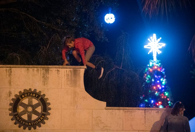 """Wyatt Burdick, 10, of Vero Beach, climbs outside The Heritage Center, as the New Year's ball and Christmas tree can be seen behind him, ahead of the Heritage Center's New Year's Eve """"Party of the Century — Diamonds Are Forever"""" event Monday, Dec. 31, 2018, in downtown Vero Beach. The evening's festivities included a ball drop, light show, live entertainment, outdoor dance floor, fireworks, food and champagne."""