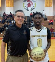 Treasure Coast High School boys basketball coach Pat Kelly presented a commemorative ball to senior guard Tyrec Thompson after reaching 1,000 career points in a Dec. 21 win against Miami Southridge in Miami-Dade County.