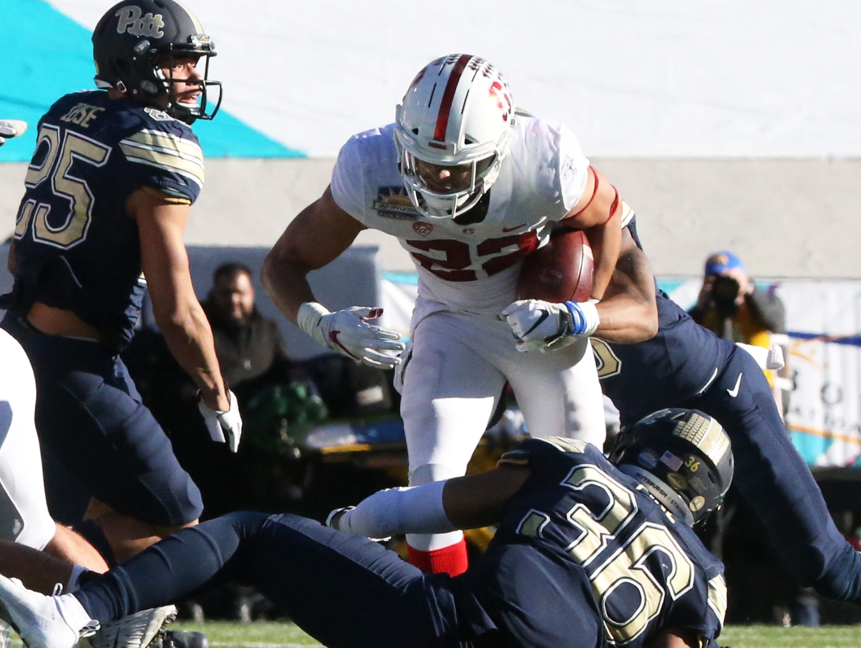 Stanford running back Cameron Scarlett, 22, gets the hand-off against Pitt Monday.