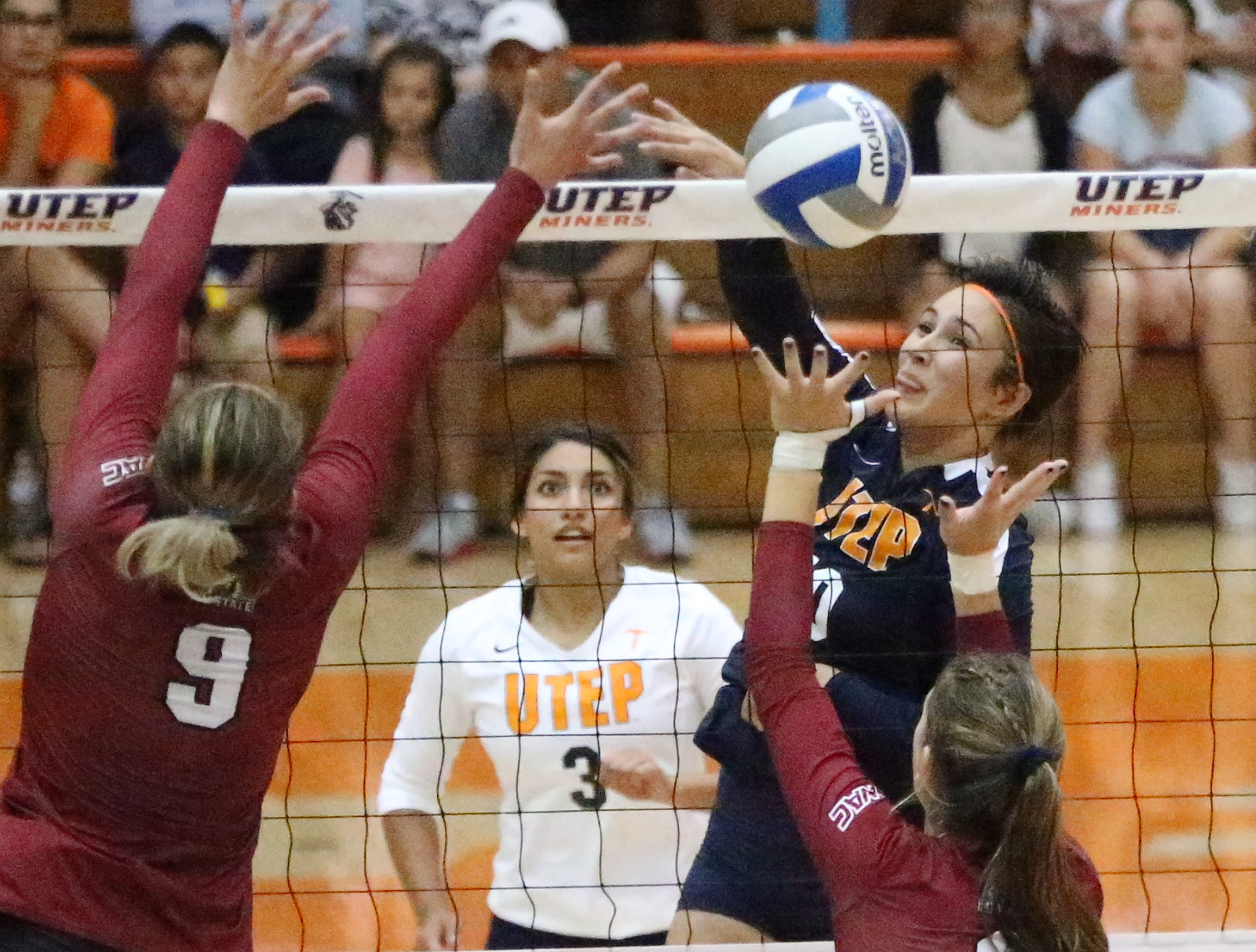 UTEP's Briana Arellano fires past Julianna Salanoa, 9, and Ashley Anselmo of NMSU Sunday in Memorial Gym. The Miners lost to the Aggies in three sets.