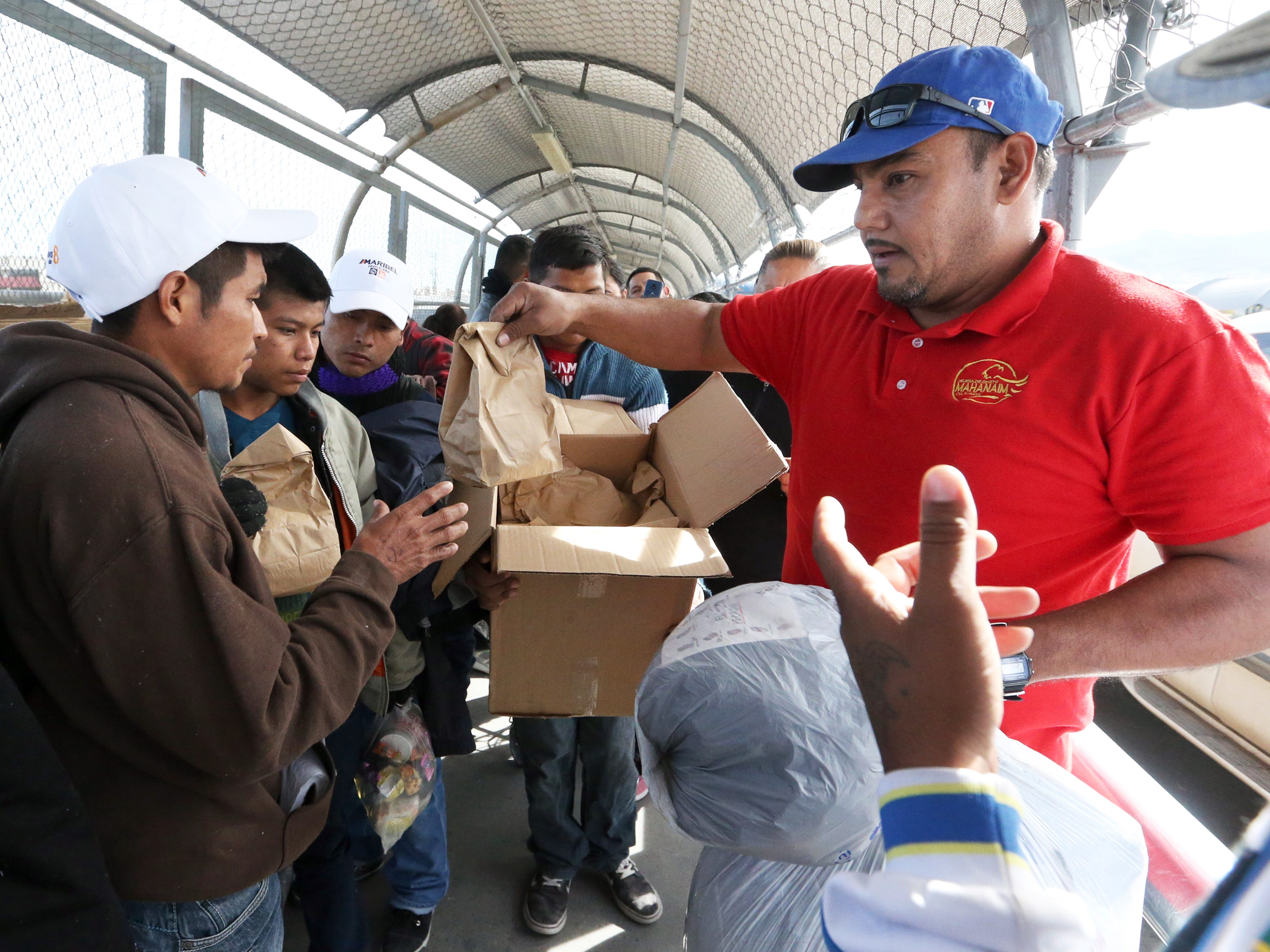 Hugo Enrique Lujan, right, of Mahanaim Christian church in Juarez hands out sack lunches to migrants waiting to enter the U.S. atop the Paso Del Norte international bridge Thursday, Nov. 1. Just over 100 immigrants from various countries, including Mexico, Central America and Cuba were camped out at the bridge. U.S. immigration officials were allowing small groups at a time to enter.