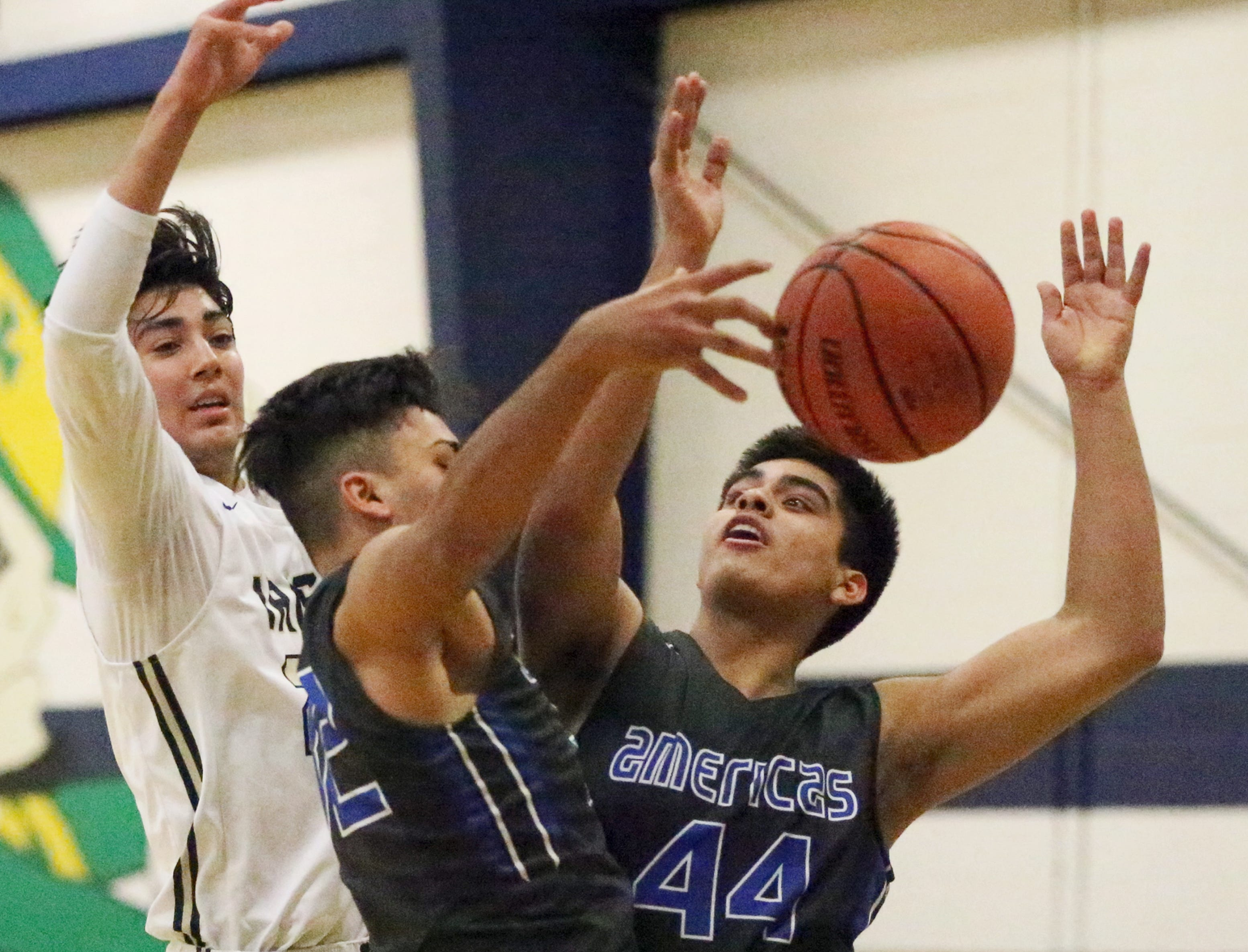 Esteban Fernandez, left, of Cathedral battles for a rebound with Christian Martinez, center, and JP Sanchez, 44, of Americas Tuesday, Nov 27 night at Cathedral.