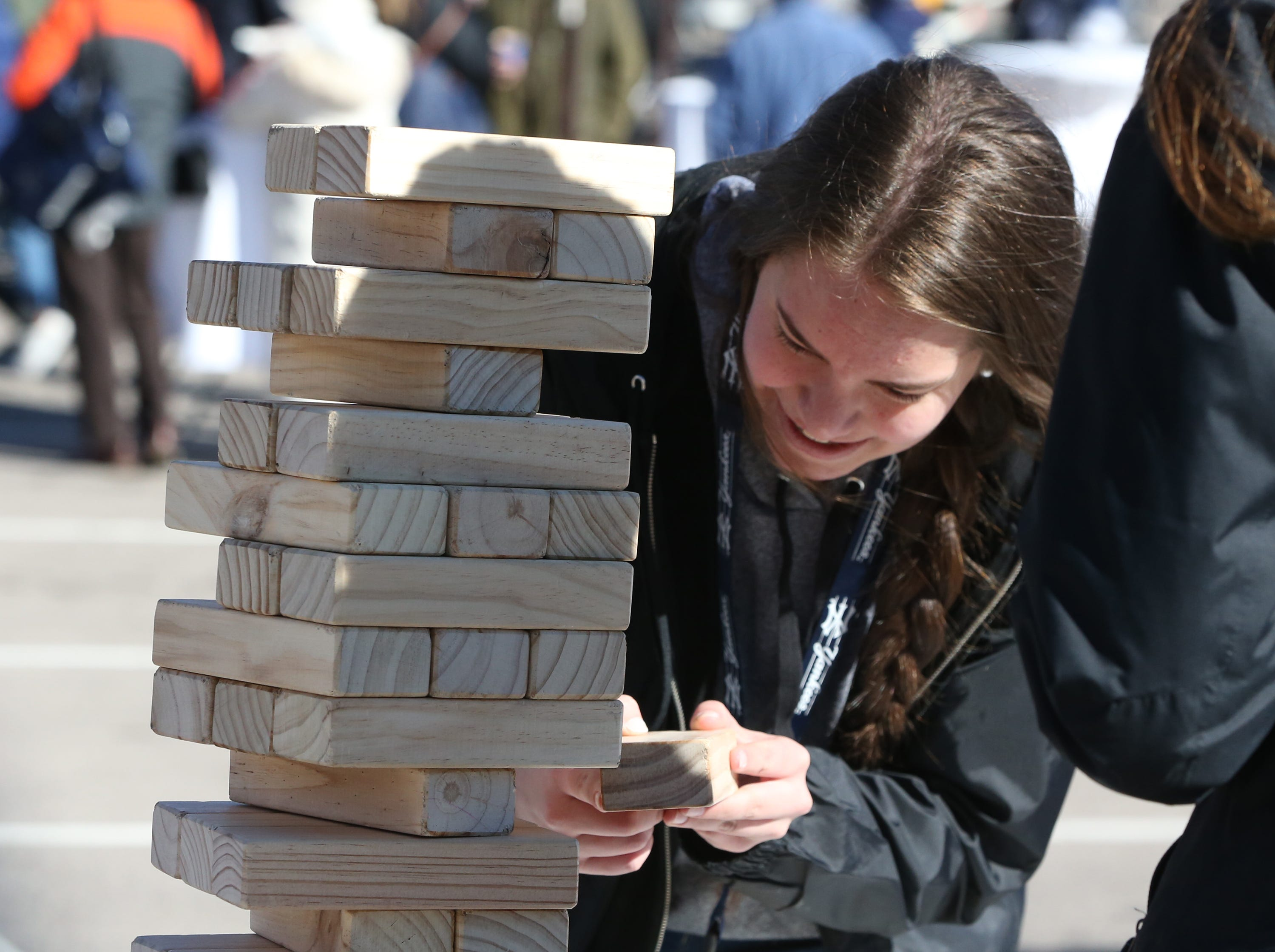 Gabriela De Santos of El Paso tries to carefully remove a stacking piece before the tower came crashing down Monday.