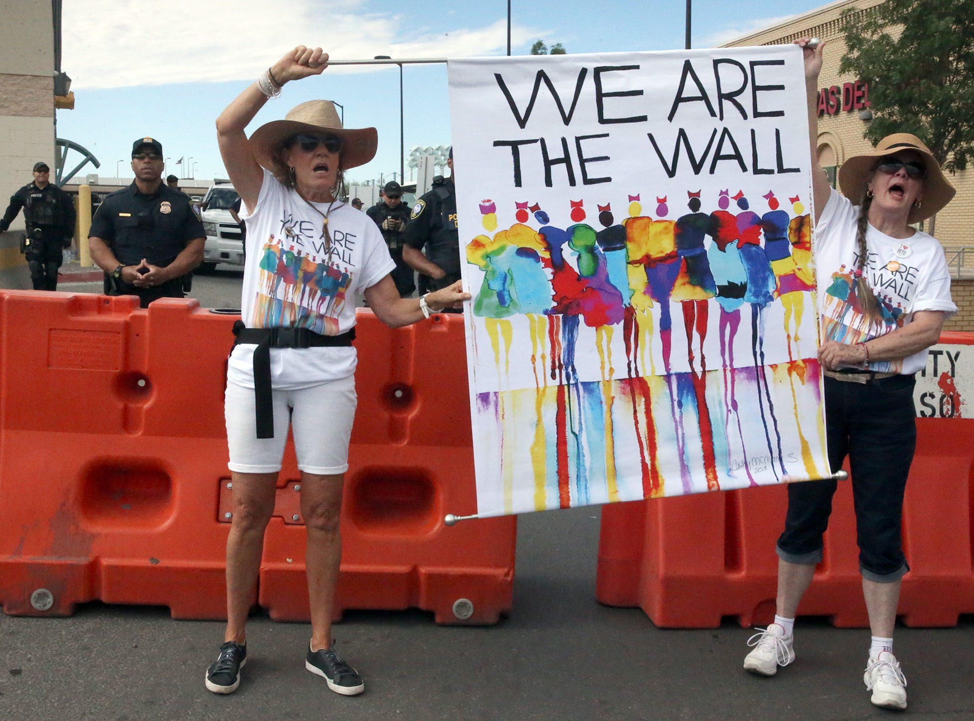 Demonstrators hold a banner in front of a barricade at the South-bound lanes to the Paso Del Norte International Port of Entry in downtown El Paso. The rally at the base of the port closed traffic for about an hour. U.S. Customs and Border Protection officers watch in background.