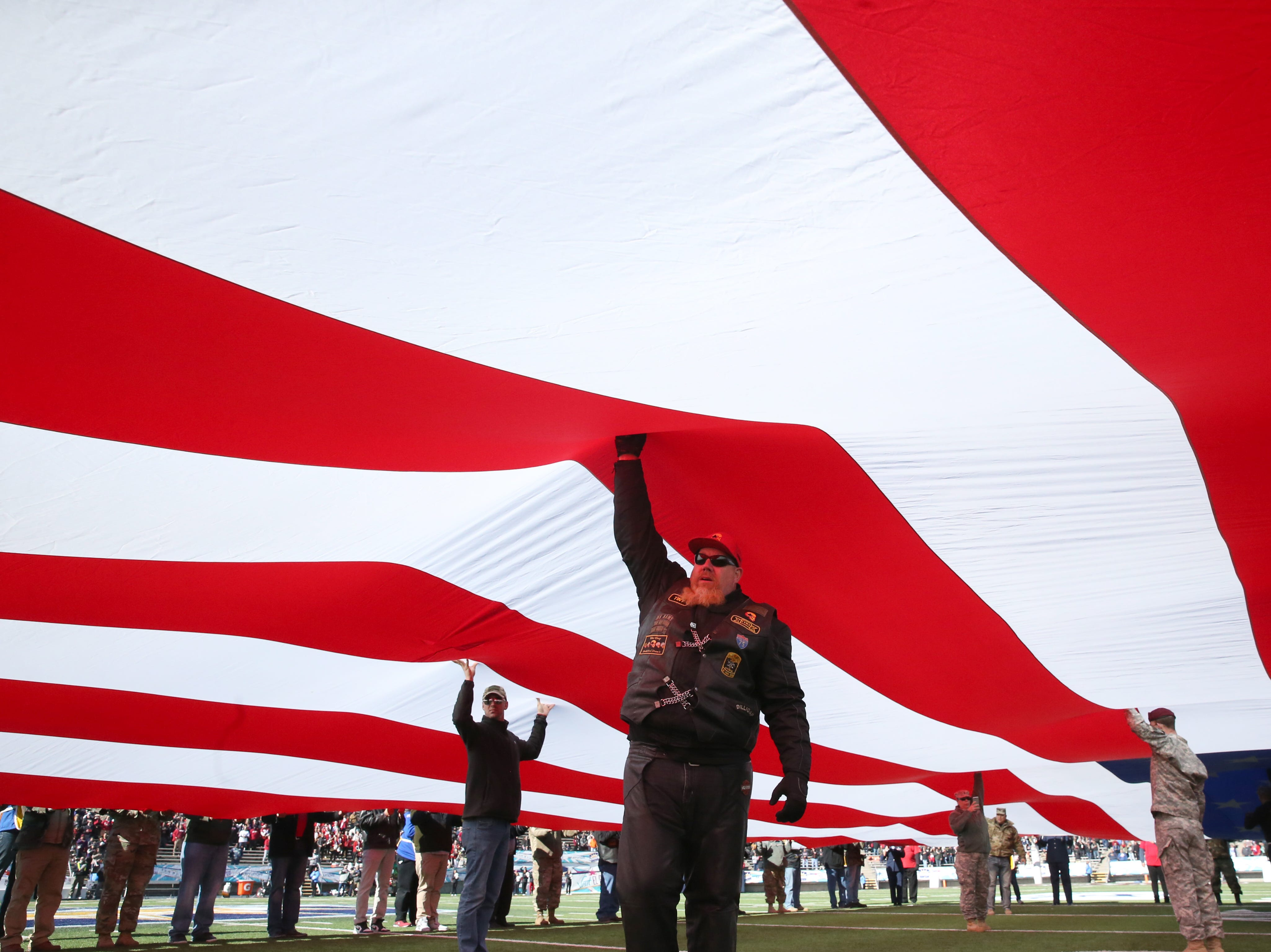 Military veterans hoist a large U.S. flag on the field during the 85th Hyundai Sun Bowl game between the Stanford Cardinal and the Pitt Panthers Monday. The Cardinal won a close game 14-13.