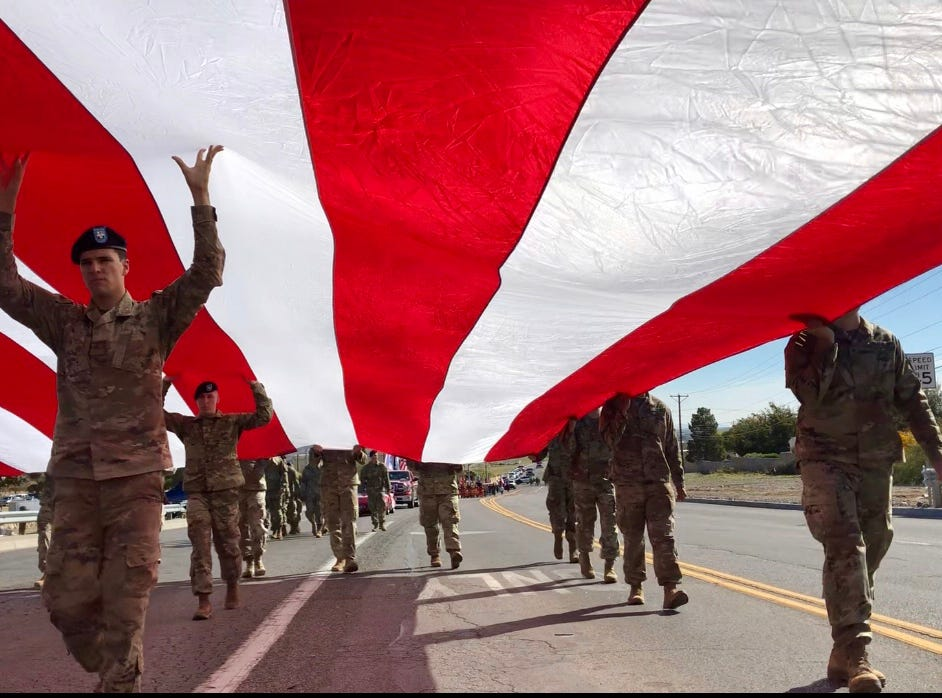Soldiers of the 4th Battalion, 17th Infantry Regiment, 1st Brigade Combat Team of the 1st Armored Division at Fort Bliss carry a giant U.S. flag along  Diana Drive to be hoisted at half staff over Old Glory Memorial during the 2018 Northeast Veteran's Day Parade Sunday, Nov. 11.