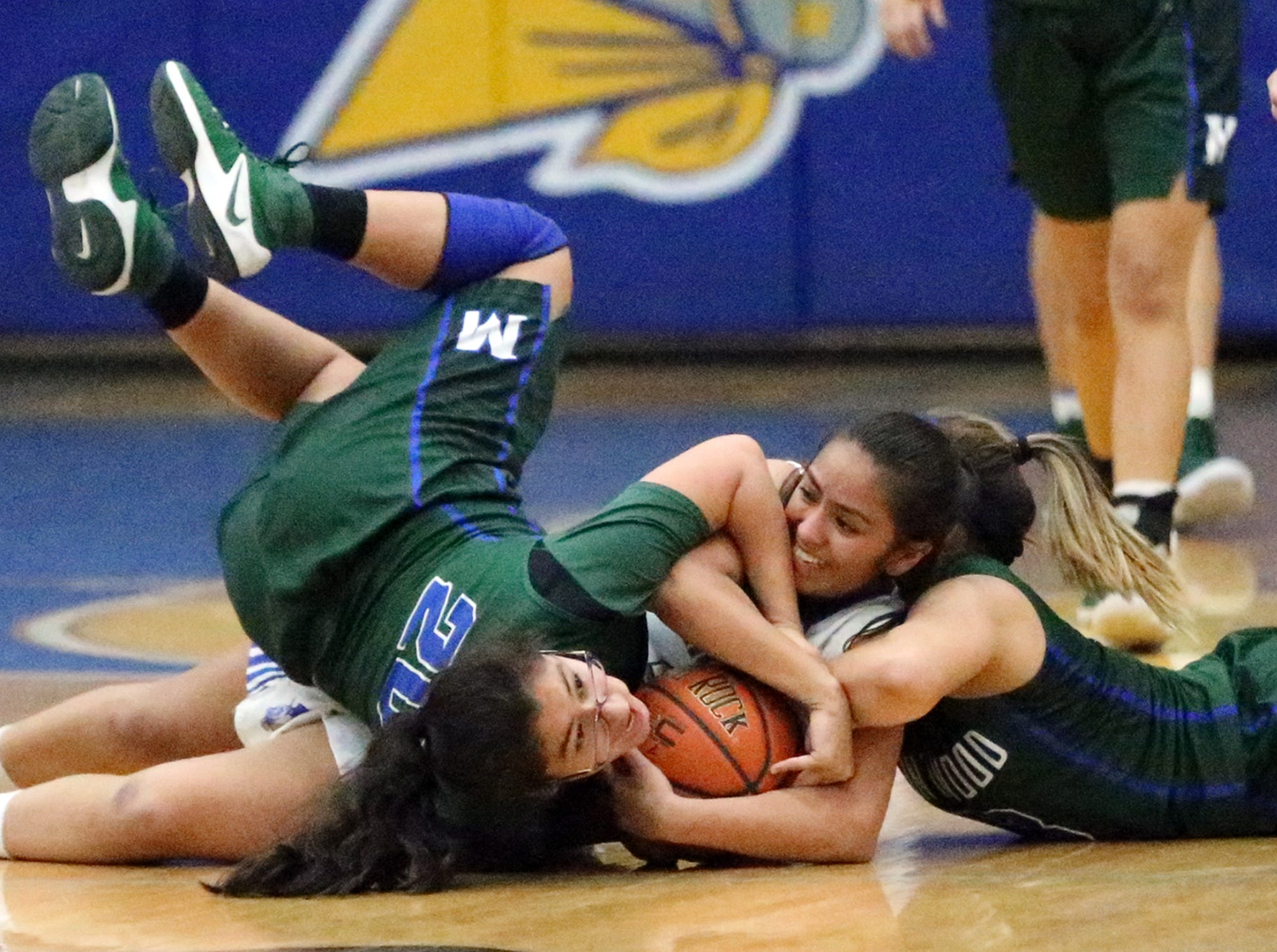 Eastwood's Danielle Blackmon, center, holds on to the ball while being challenged by Montwood's Sarahi Ramirez, left, and Akeala Rodriguez, right, during their game Tuesday night at Eastwood. The Troopers routed the Rams 53-27.