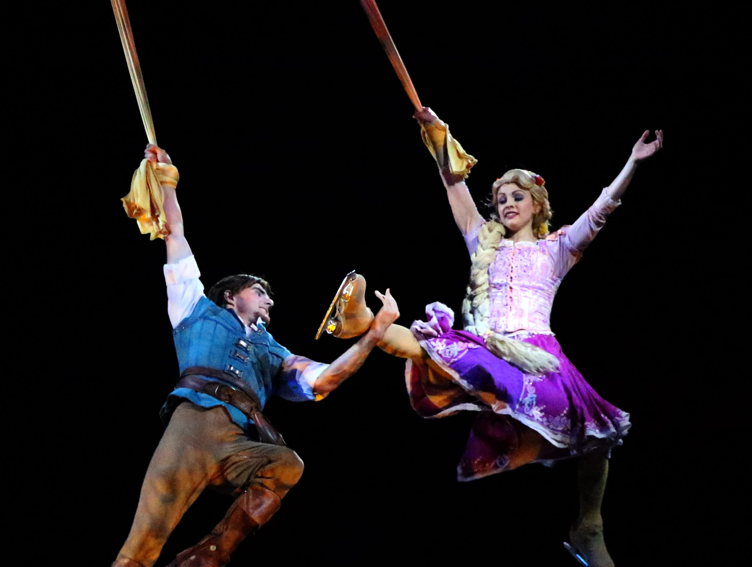 Rapunzel and a prince spin in the air over the ice in this scene from the Disney On Ice presentation of 'Dare to Dream' during its opening night Wednesay, Oct. 3 at the El Paso County Coliseum.