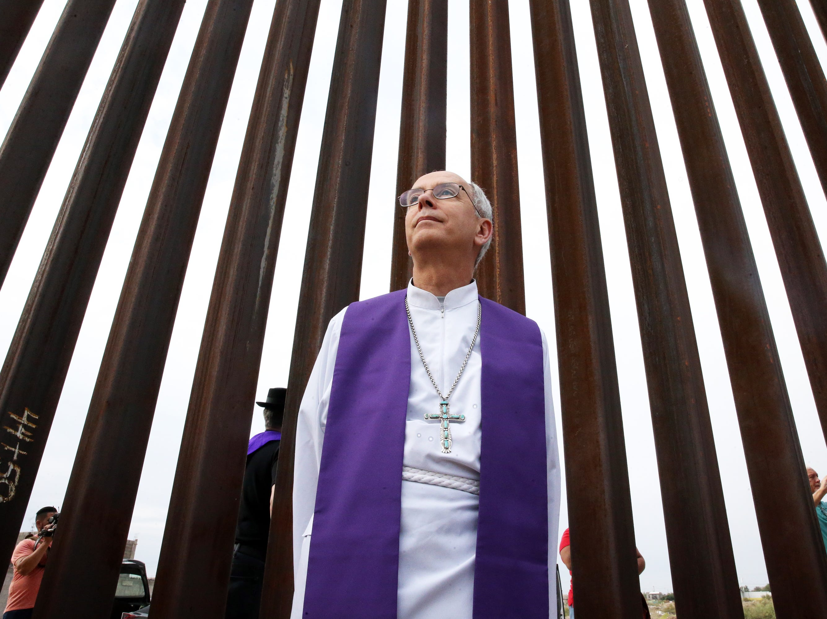 El Paso Catholic Bishop Mark Seitz stands along side the border fence at Sunland Park, N.M. during a interfaith gathering of clergy, many visiting from other parts of the country where they spoke, prayed and visited with people gathered on the Juarez side.