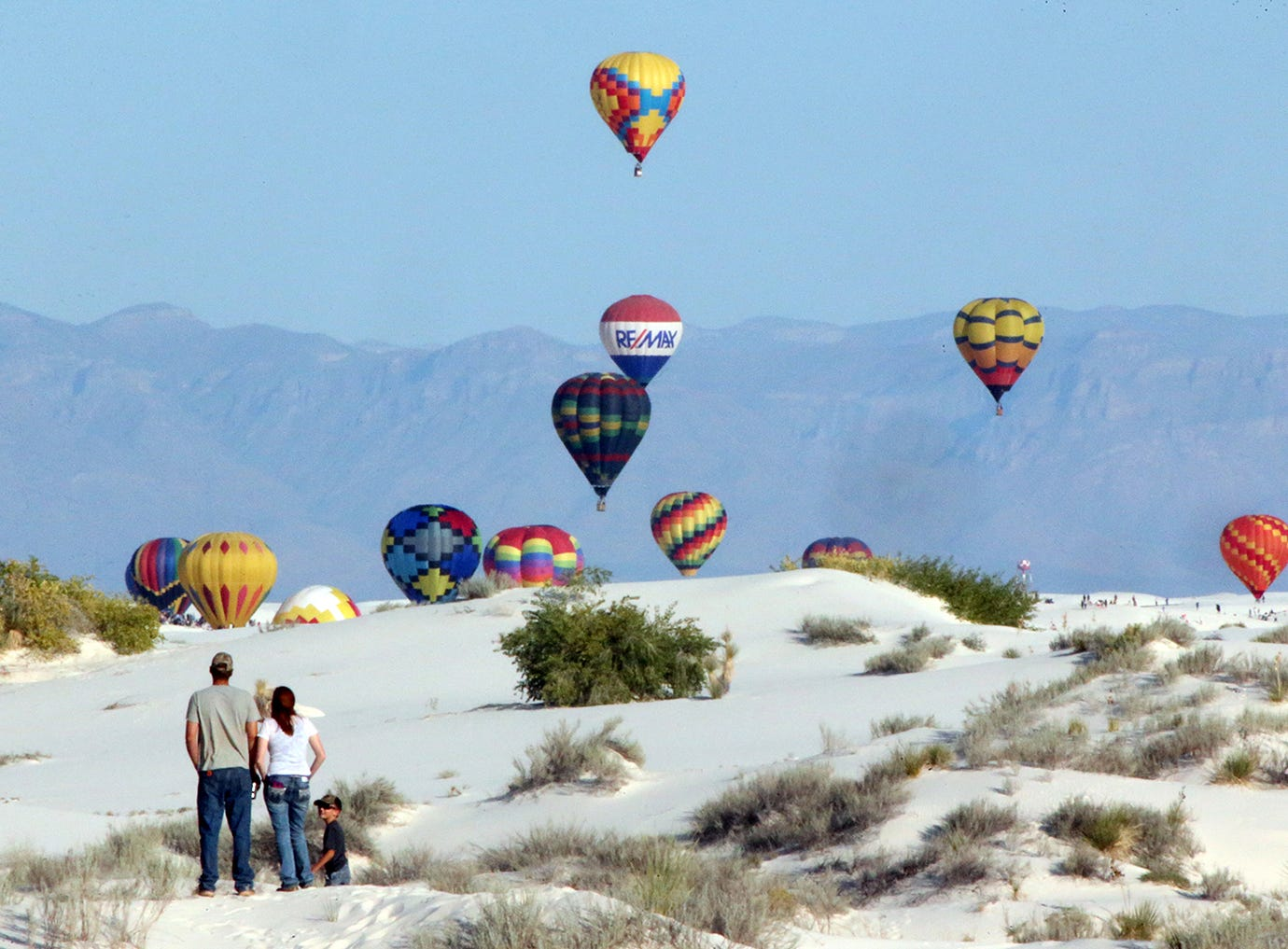 Hot air balloons go aloft over the dunes during the 2018 White Sands Balloon Invitational Saturday, Sept. 15 at White Sands National Monument.  A long trail of vehicles snaked into the monument with people setting up viewing positions with chairs and umbrellas atop the dunes.