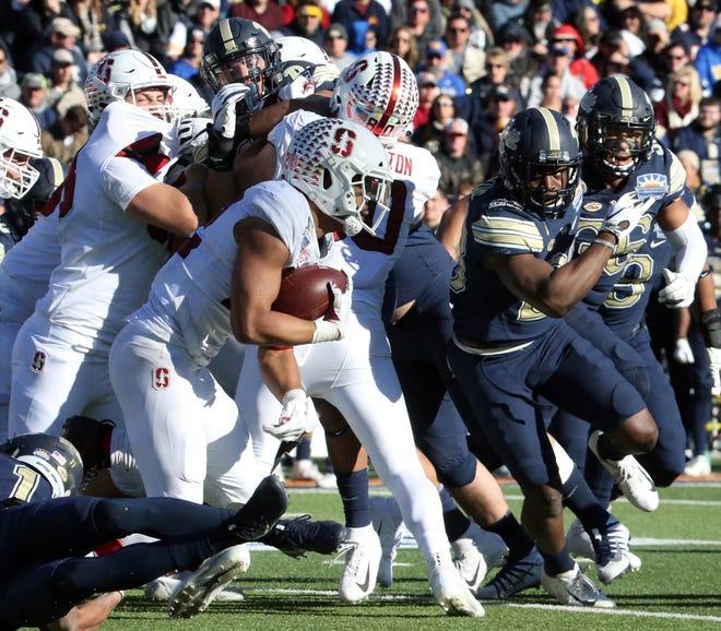 Stanford running back Cameron Scarlett scrambles following a handoff against Pitt Monday.