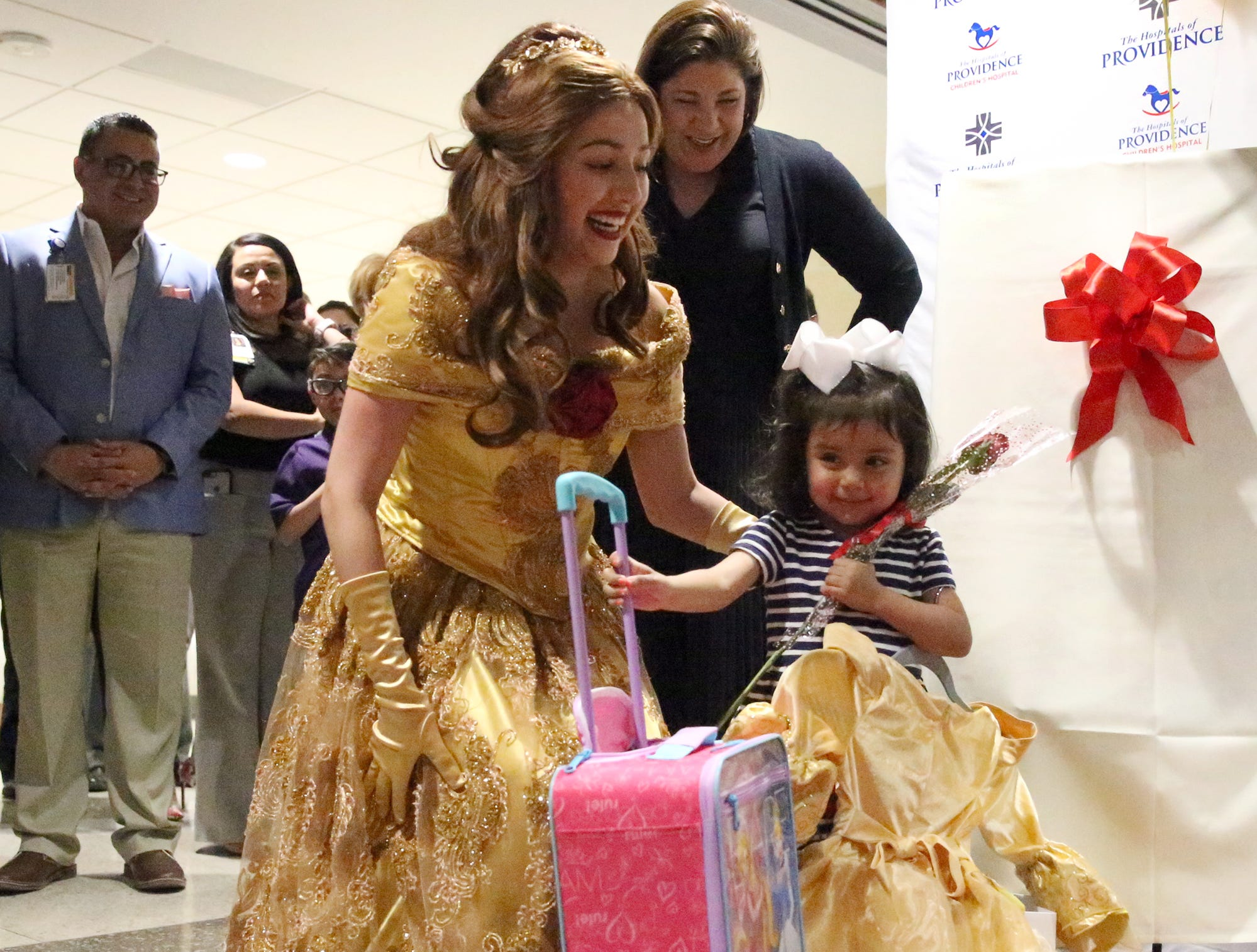 "Fernanda Rivera, 3, is presented with luggage and a dress by the Make-A-Wish Foundation at the Children's Hospital at Providence Wednesday. Melissa Diaz, left, of Dreams Come True Princess Parties dressed as Belle of ""Beauty and the Beast"" with Sally Deitch, top, Group CEO for the Hospitals of Providence. The youngster and her family will visit Walt Disney World."
