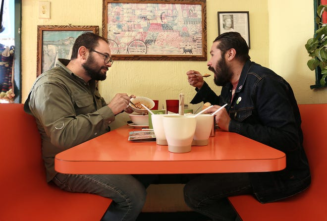 Christ Chavez, left, and Tavo Vielma eat menudo on New Year's Day at Jalisco Cafe in the Segundo Barrio as they awaited the drawing for free menudo for a year. The restaurant touts itself as the world menudo headquarters and holds the drawing every new year's day.