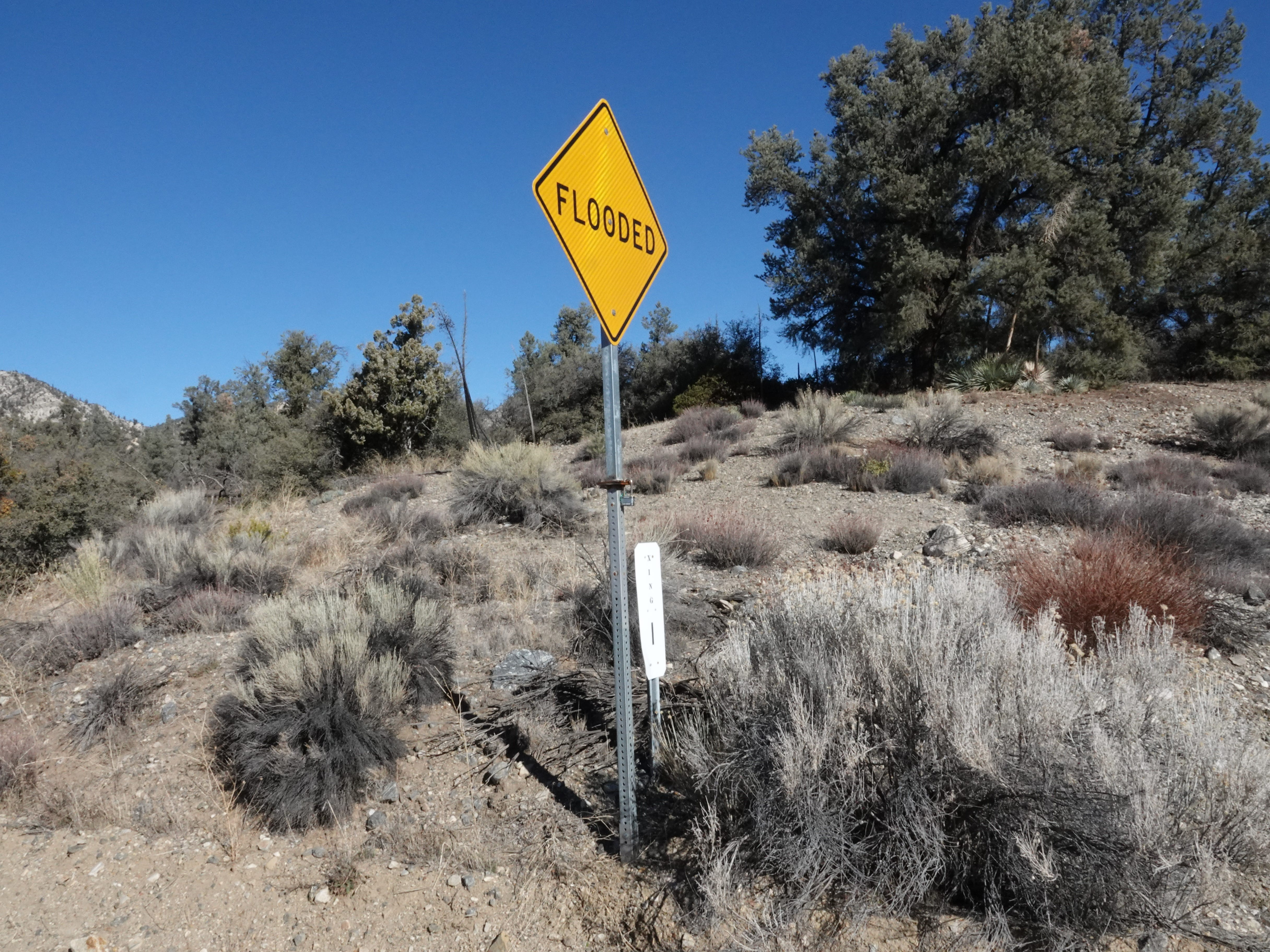 "The small white sign next to the ""flooded"" warning marks crossing No. 1 on Lockwood Valley Road, helping Ventura County sheriff's deputies navigate remote terrain during emergencies."
