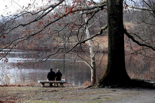 George Storer of Manhattan and Daniela Gomez of White Plains enjoy an unseasonably warm New Year's Day as they relaxed on a bench overlooking Swan Lake at Rockefeller State Park Preserve in Mt. Pleasant Jan. 1, 2019.
