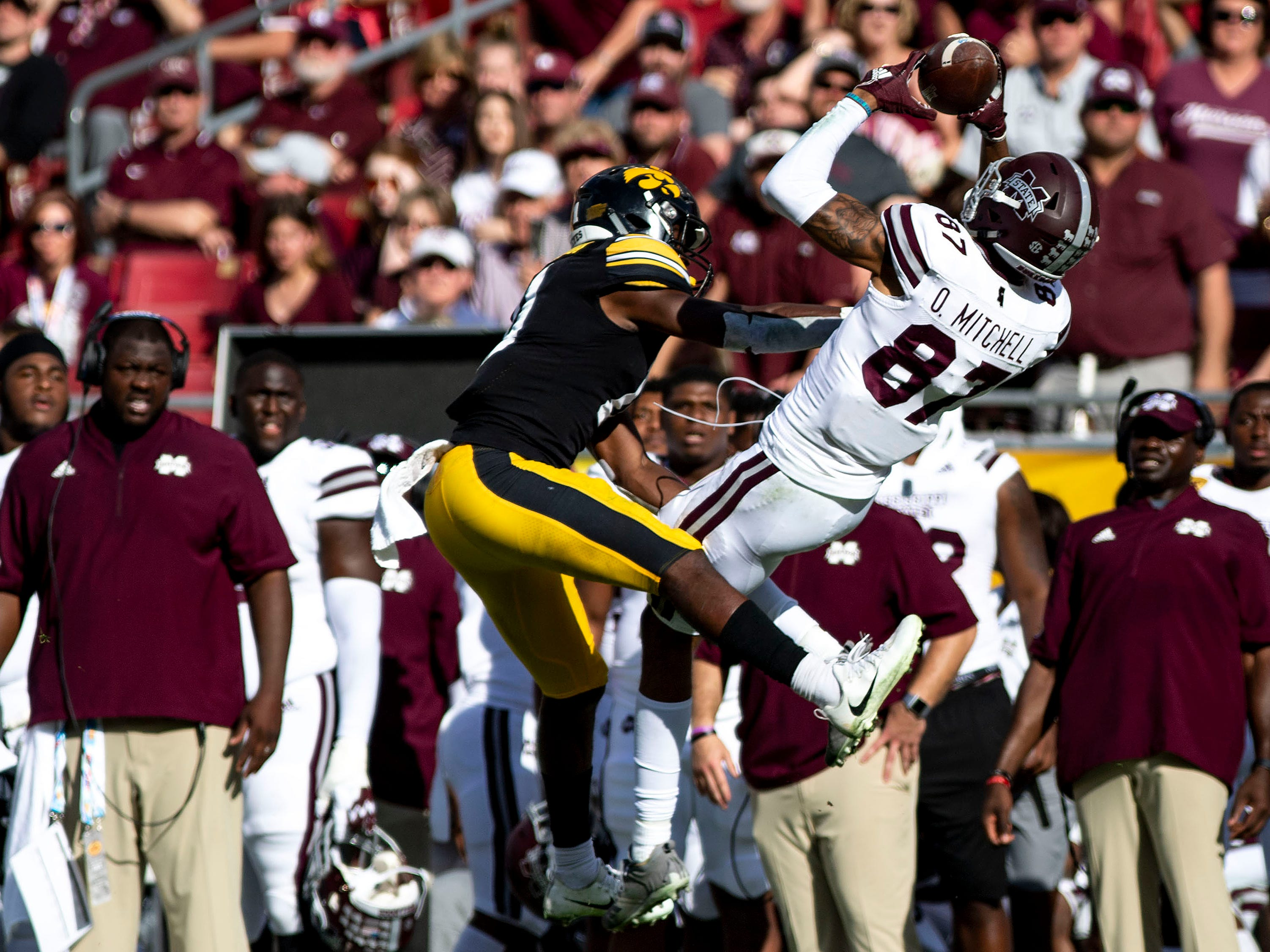Mississippi State wide receiver Osirus Mitchell makes a reception in front of Iowa defensive back Michael Ojemudia  during the fourth quarter of the 2019 Outback Bowl.