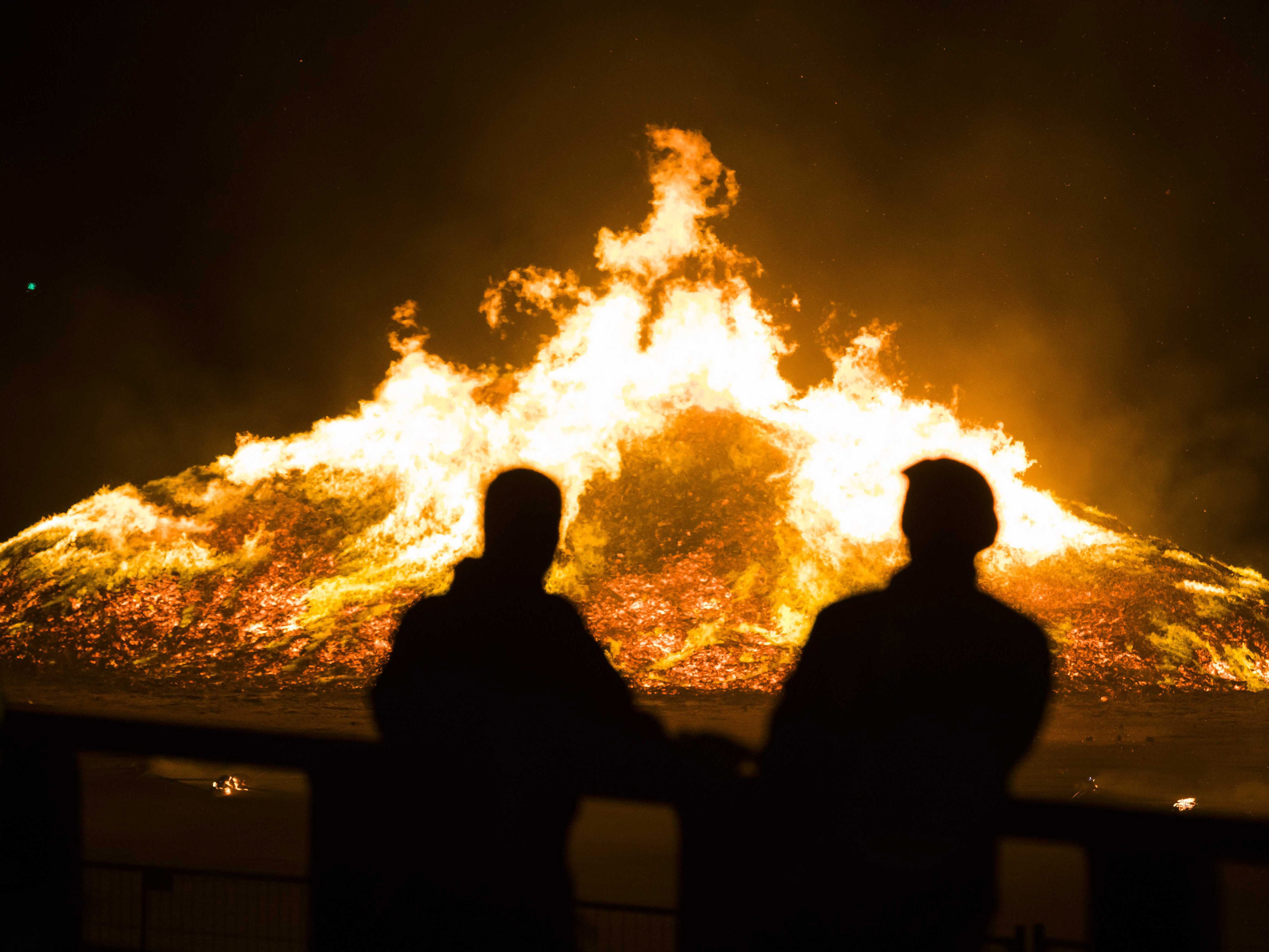 People look at a bonfire on the beach set up to celebrate the turn of the year on New Year's Eve, in Scheveningen, coastal district of The Hague, Netherlands on Jan. 1, 2019. The bonfire got out of control as ash was blown from a bonfire towards spectators and homes in a near district.