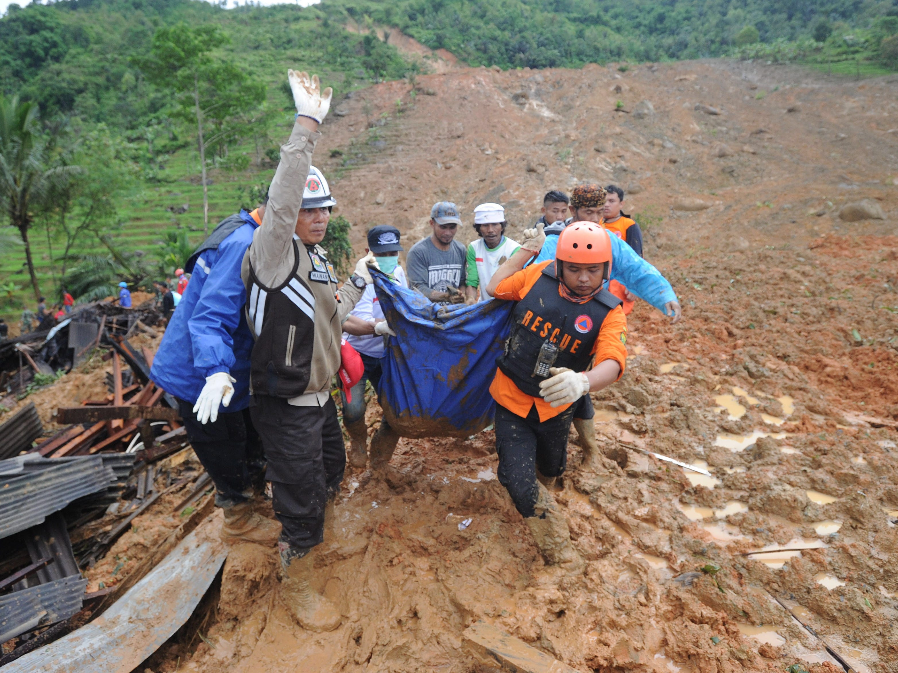 Rescuers carry the remains of a landslide victim at Sirnaresmi village in Sukabumi, Indonesia on Jan 1, 2019.