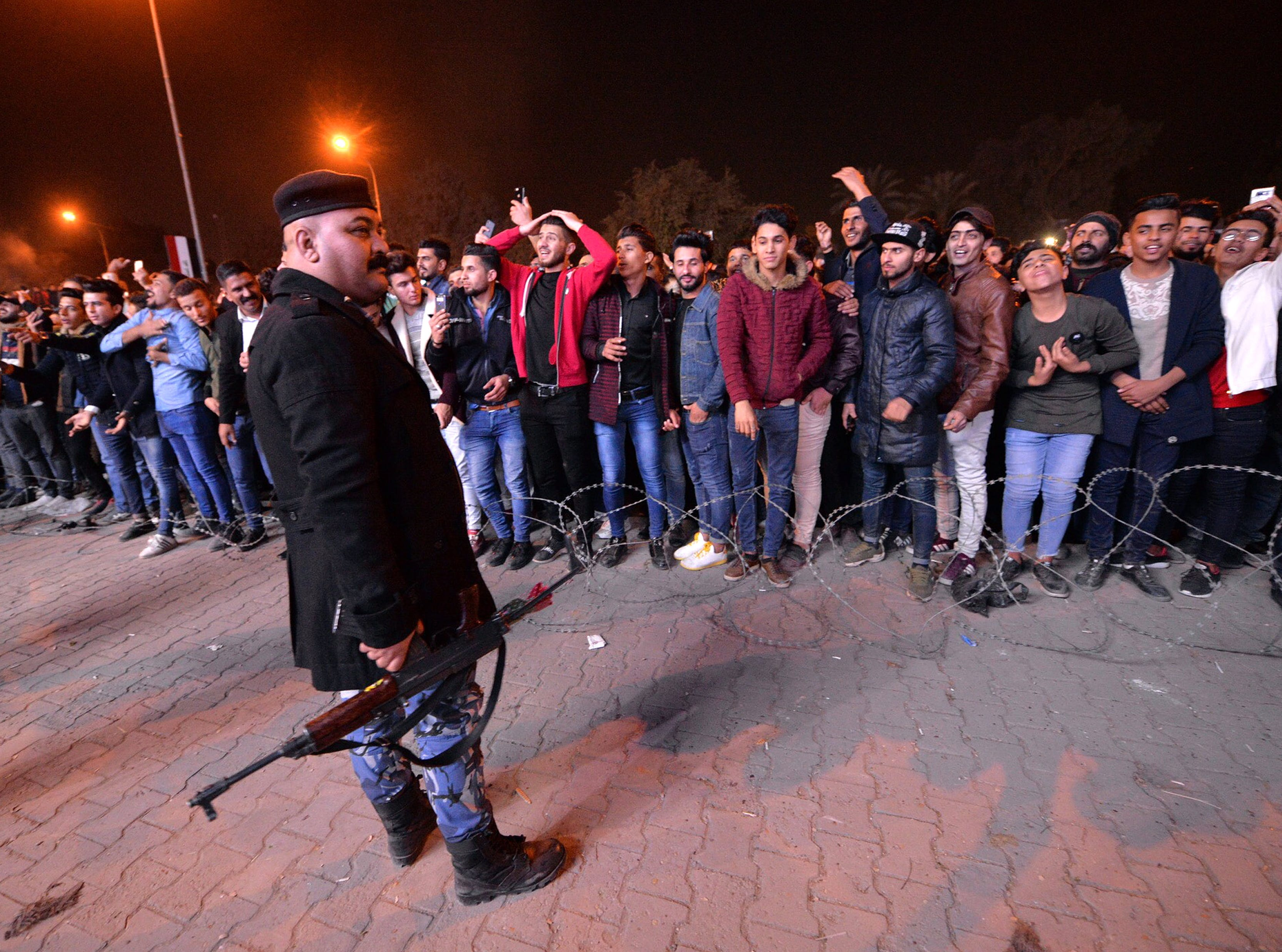 An armed Iraqi policeman stands guard as Iraqis celebrate the New Year 2019 in Baghdad, Iraq, on early Jan. 1, 2019.