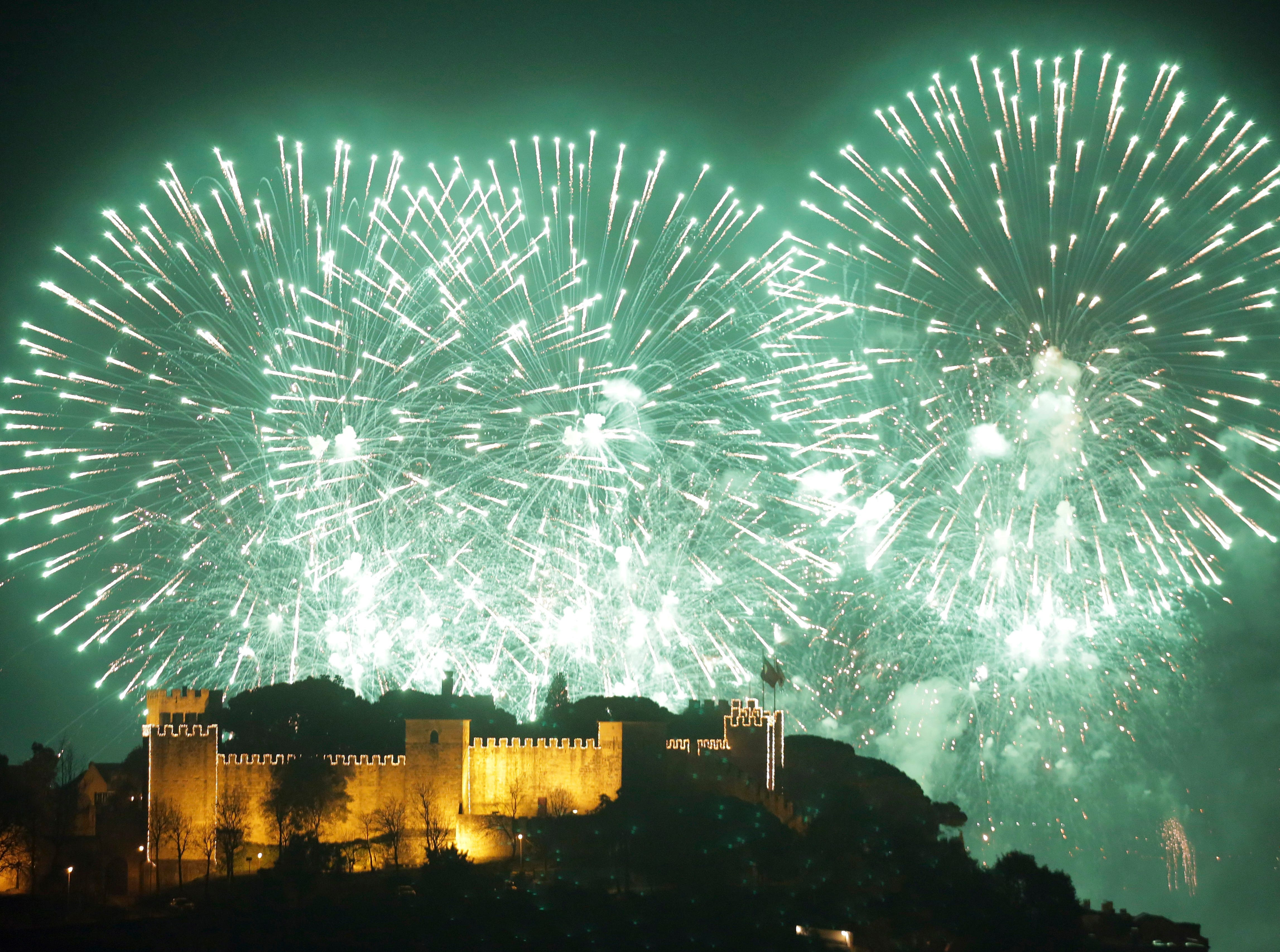 Fireworks light the sky marking New Year, behind Lisbon's Saint George castle in the first minutes of Tuesday, Jan. 1, 2019.