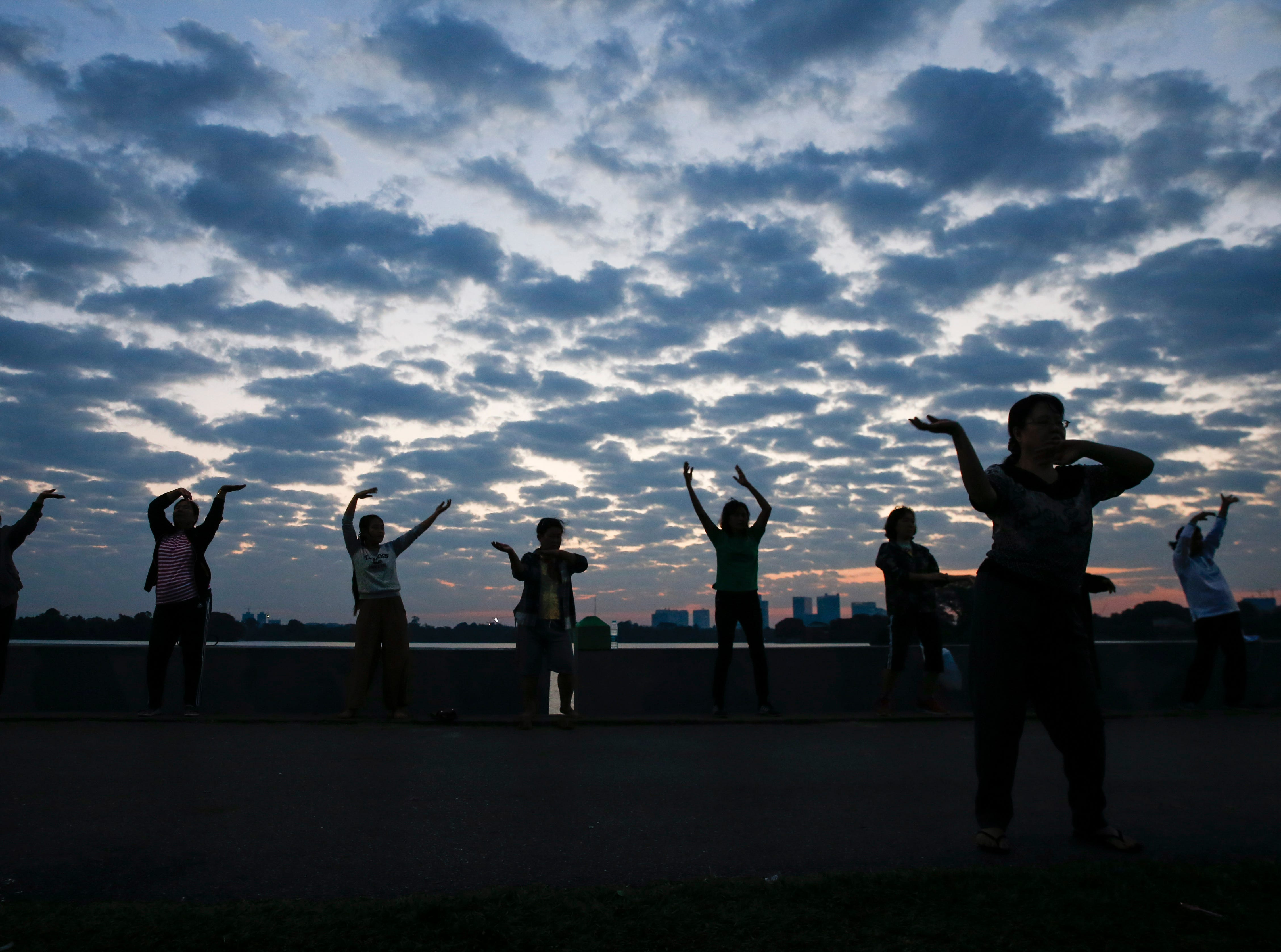 People exercises on the bank of Inya Lake during the dawn of the New Year in Yangon, Myanmar on Jan. 1, 2019.