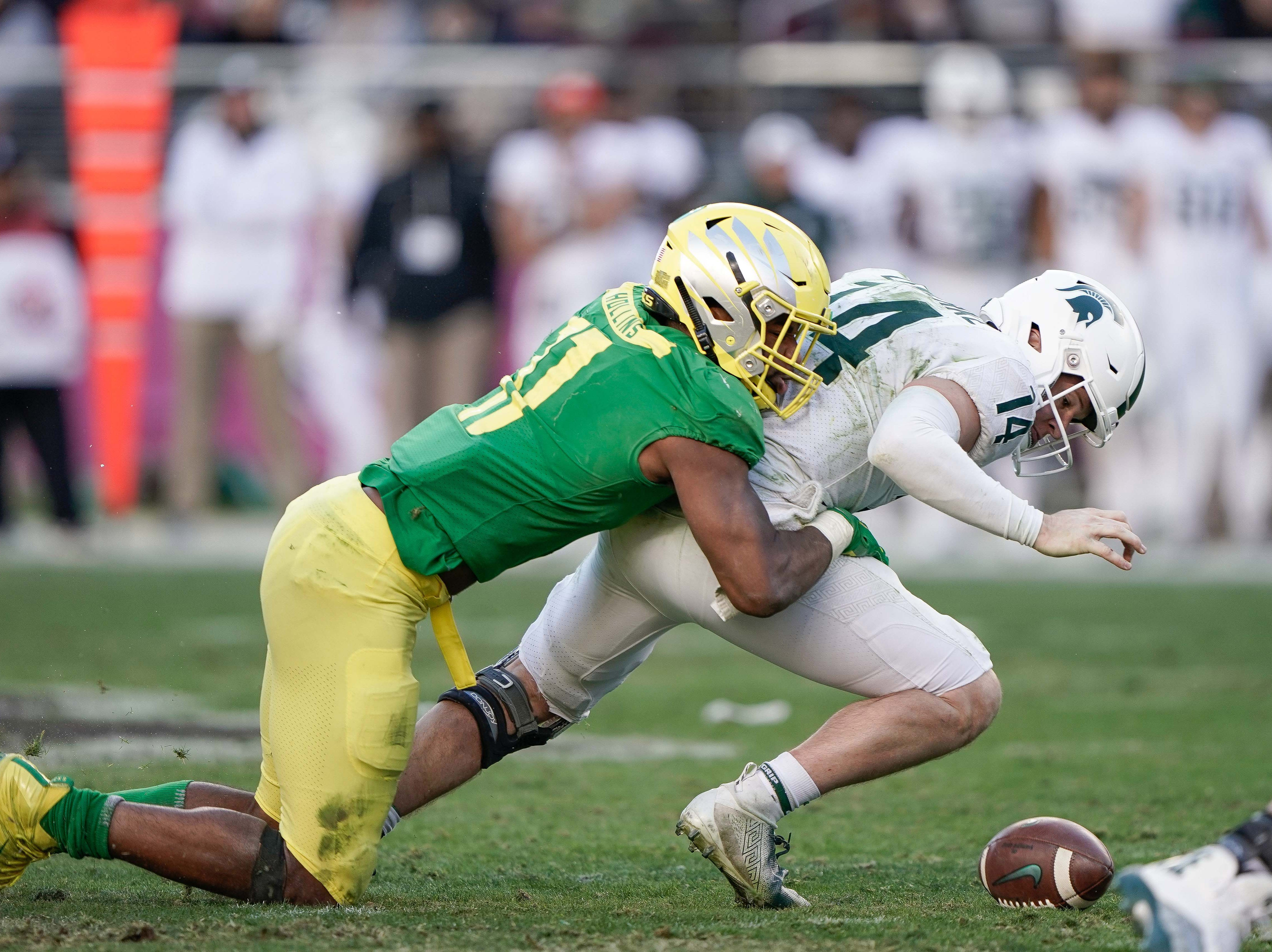 Oregon Ducks linebacker Justin Hollins (11) forces a fumble by Michigan State Spartans quarterback Brian Lewerke (14) during the fourth quarter of the Redbox Bowl.