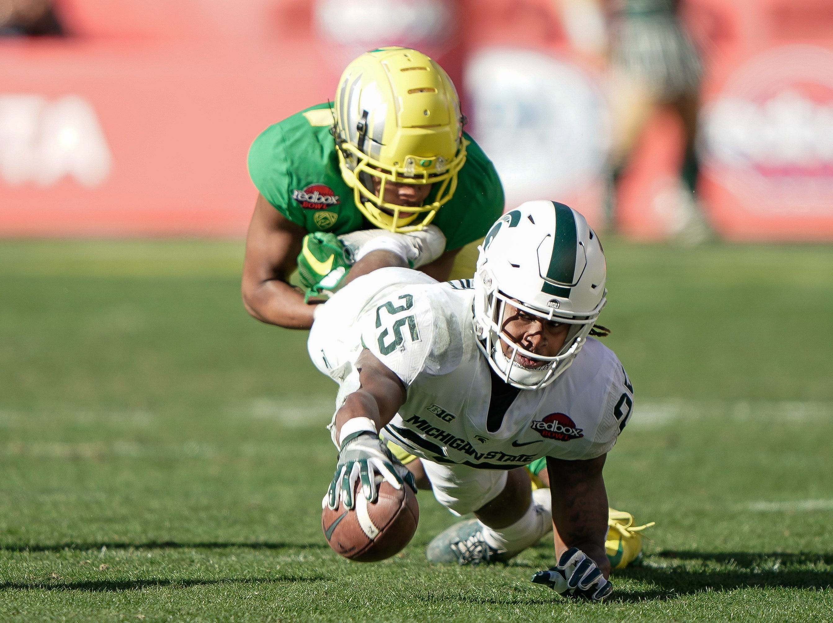 Oregon Ducks cornerback Thomas Graham Jr. (4) tackles Michigan State Spartans wide receiver Darrell Stewart Jr. (25) during the Redbox Bowl.