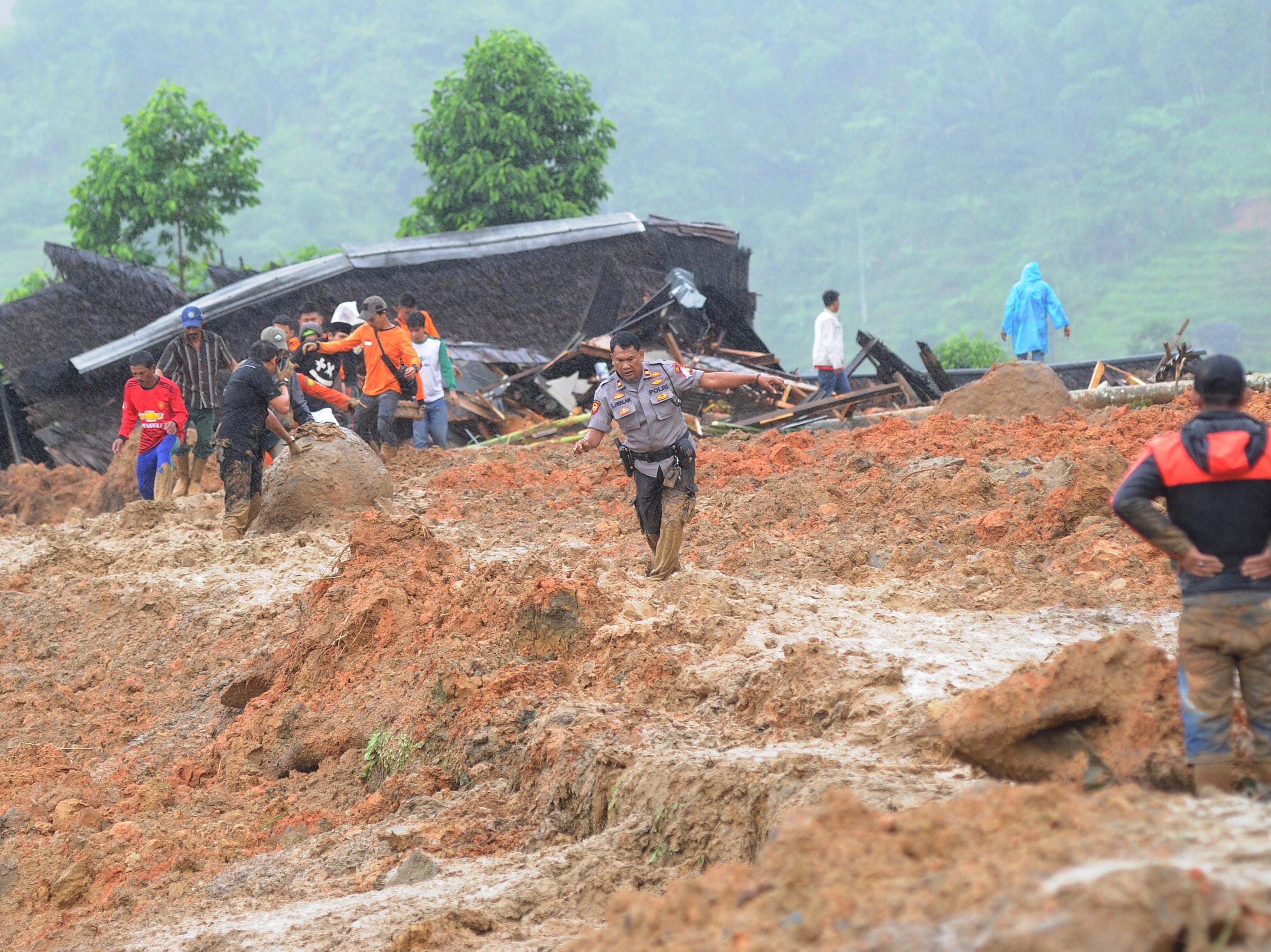 Indonesian villagers and rescuers search for landslide victims at Sirnaresmi village in Sukabumi, Indonesia on Jan. 1, 2019.