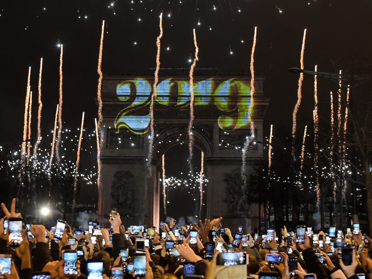 People take pictures with their mobile phones of fireworks exploding over the Arc de Triomphe on the Champs-Elysees for New Year's celebrations in the French capital Paris on Jan. 1, 2019.