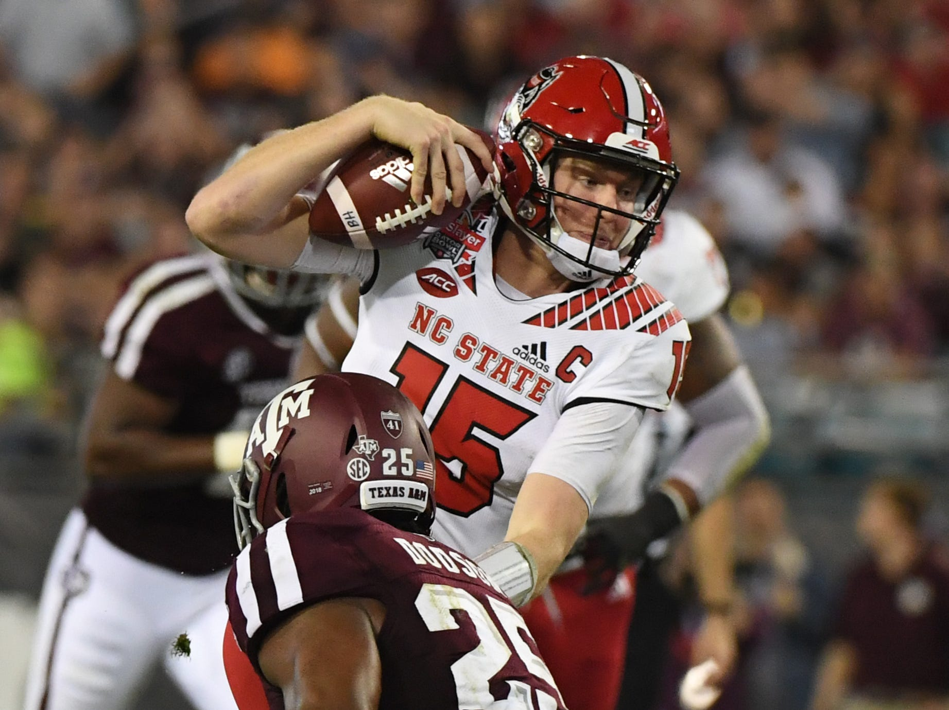 North Carolina State Wolfpack quarterback Ryan Finley (15) carries the ball against Texas A&M Aggies linebacker Tyrel Dodson (25) during the second quarter of the Gator Bowl.
