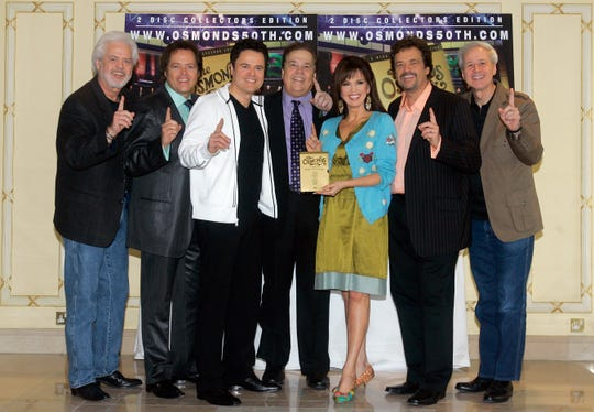 The Osmonds (from left, Merrill, Jimmy, Donny, Alan, Marie, Jay and Wayne) pose for photographers during a U.K. tour in 2008.