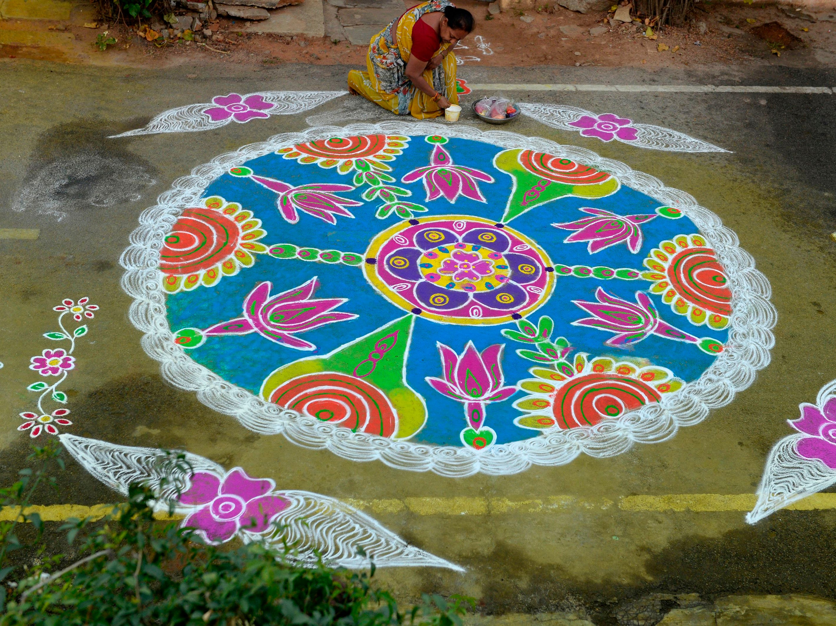 """A woman applies colored powder to a """"rangoli"""", a Hindu ritual design, to usher in the New Year in front of a home in Hyderabad on Jan. 1, 2019. Rangolis are drawn in front of homes early in the morning to welcome relatives and friends to mark the new year."""