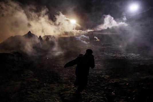 Migrants run from tear gas