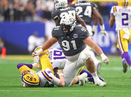 Central Florida defensive lineman Joey Connors stands over LSU quarterback Joe Burrow after a block during the first quarter of the 2019 Fiesta Bowl.