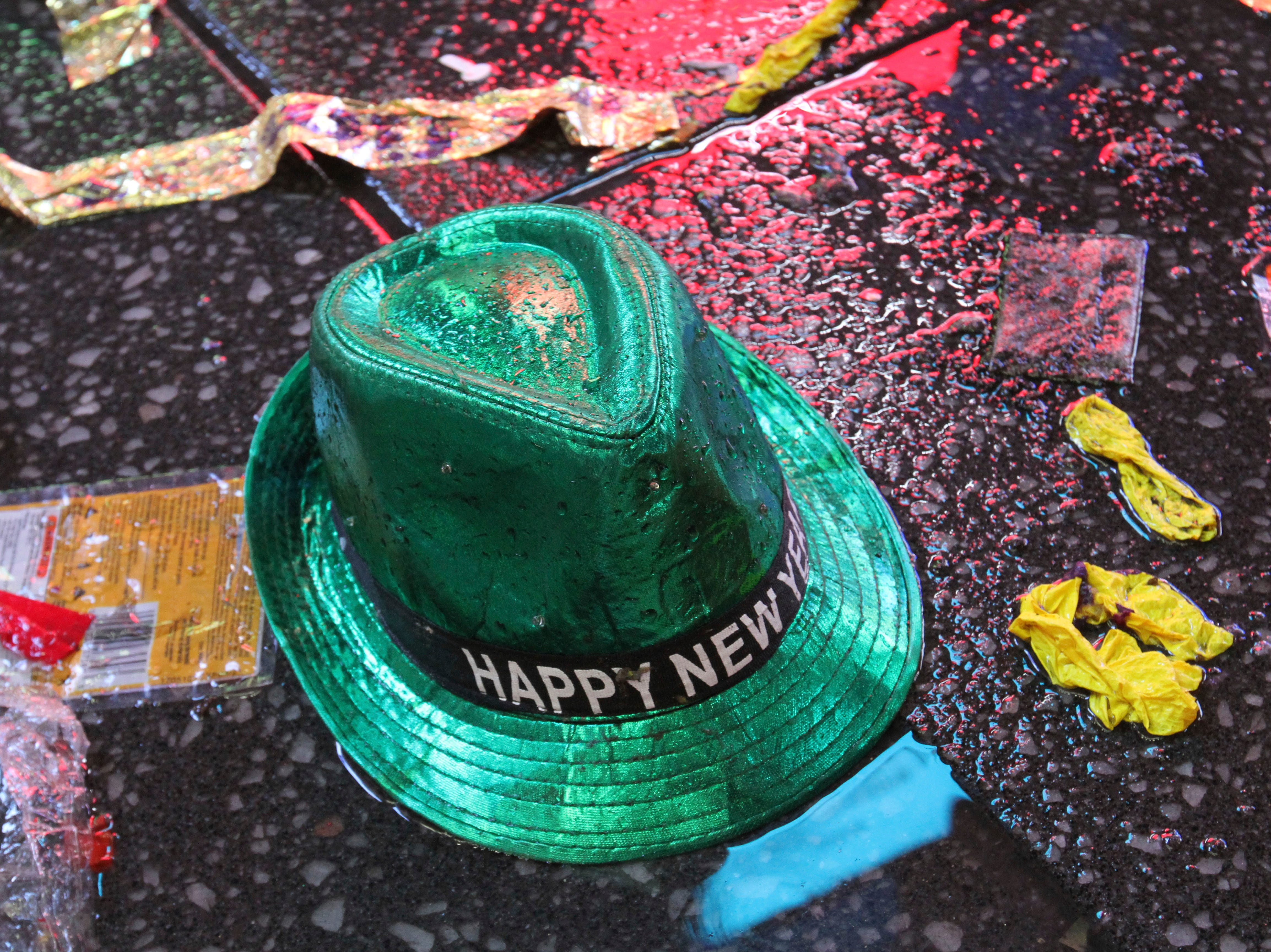 """A """"Happy New Year"""" hat lies on the wet ground along with other items following the celebration in New York's Times Square, early Tuesday, Jan. 1, 2019."""