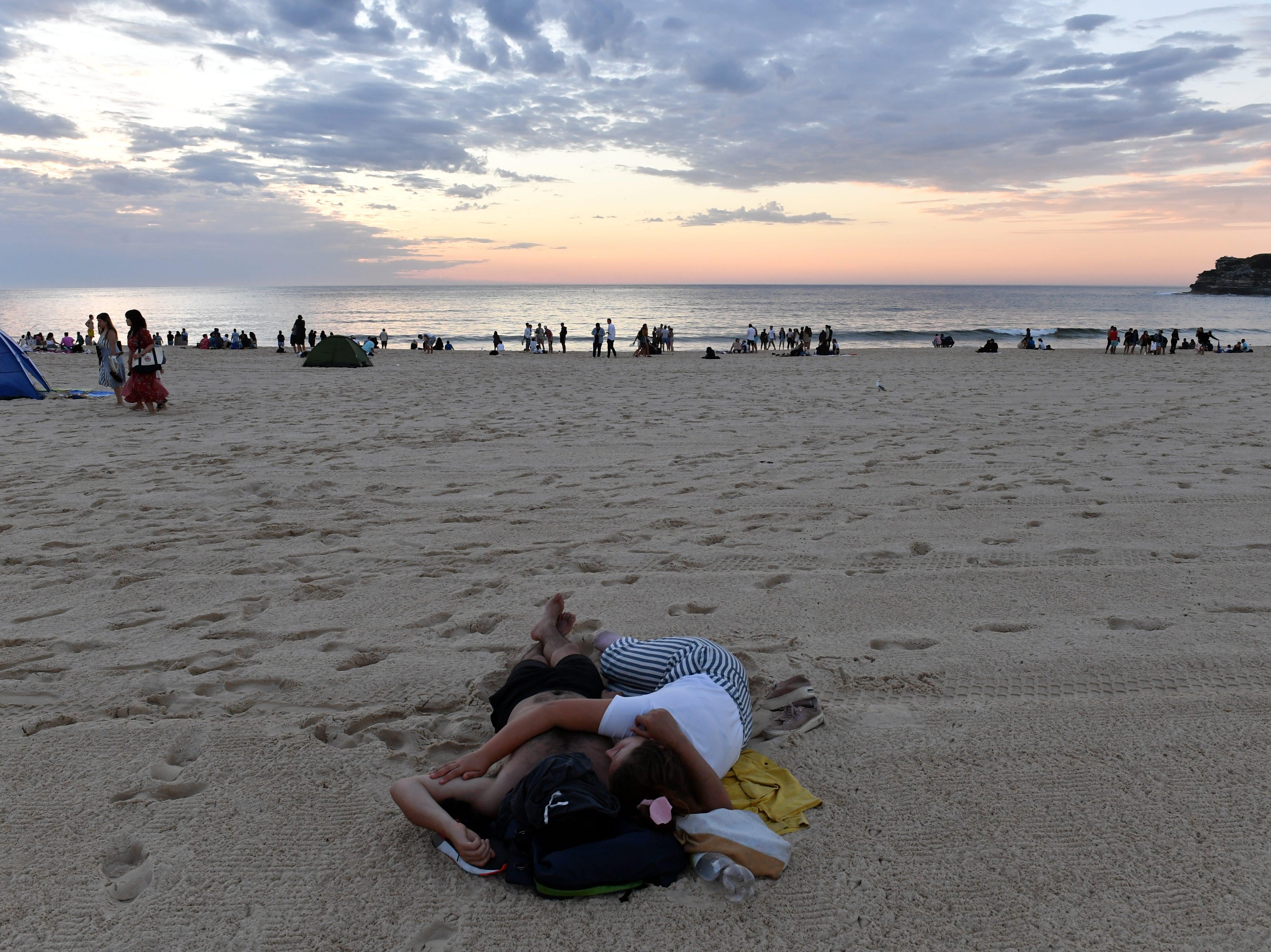 Revelers sleep on the stand during sunrise on New Year's Day at Bondi Beach in Sydney, Australia on Jan.1, 2018.