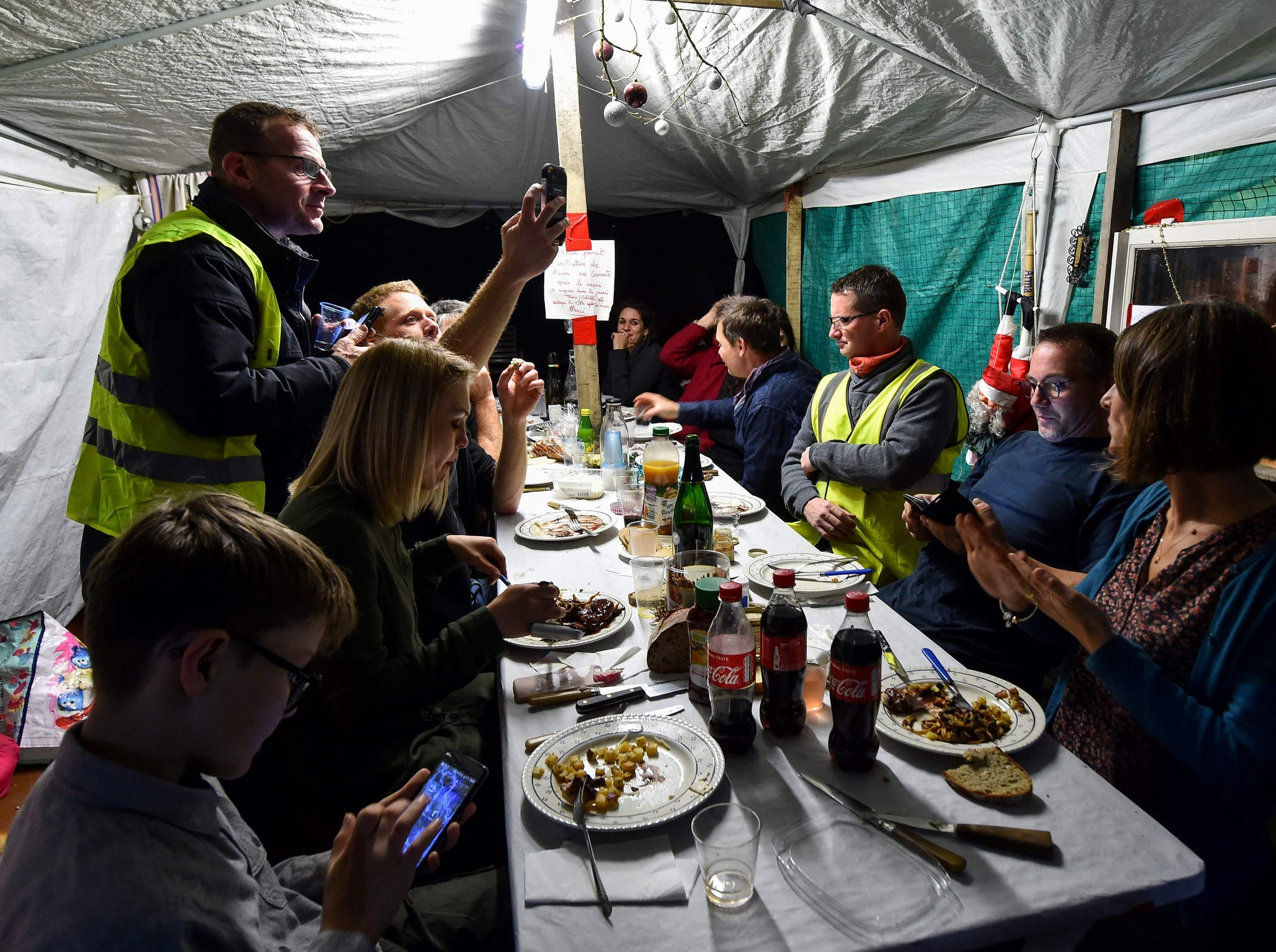 """""""Yellow vest"""" (Gilets jaunes) protestors share a New Year's Eve dinner in a makeshift shelter built of wooden palettes, on the edge of the access of the A28 motorway, south of Le Mans, northwestern France, on Monday."""