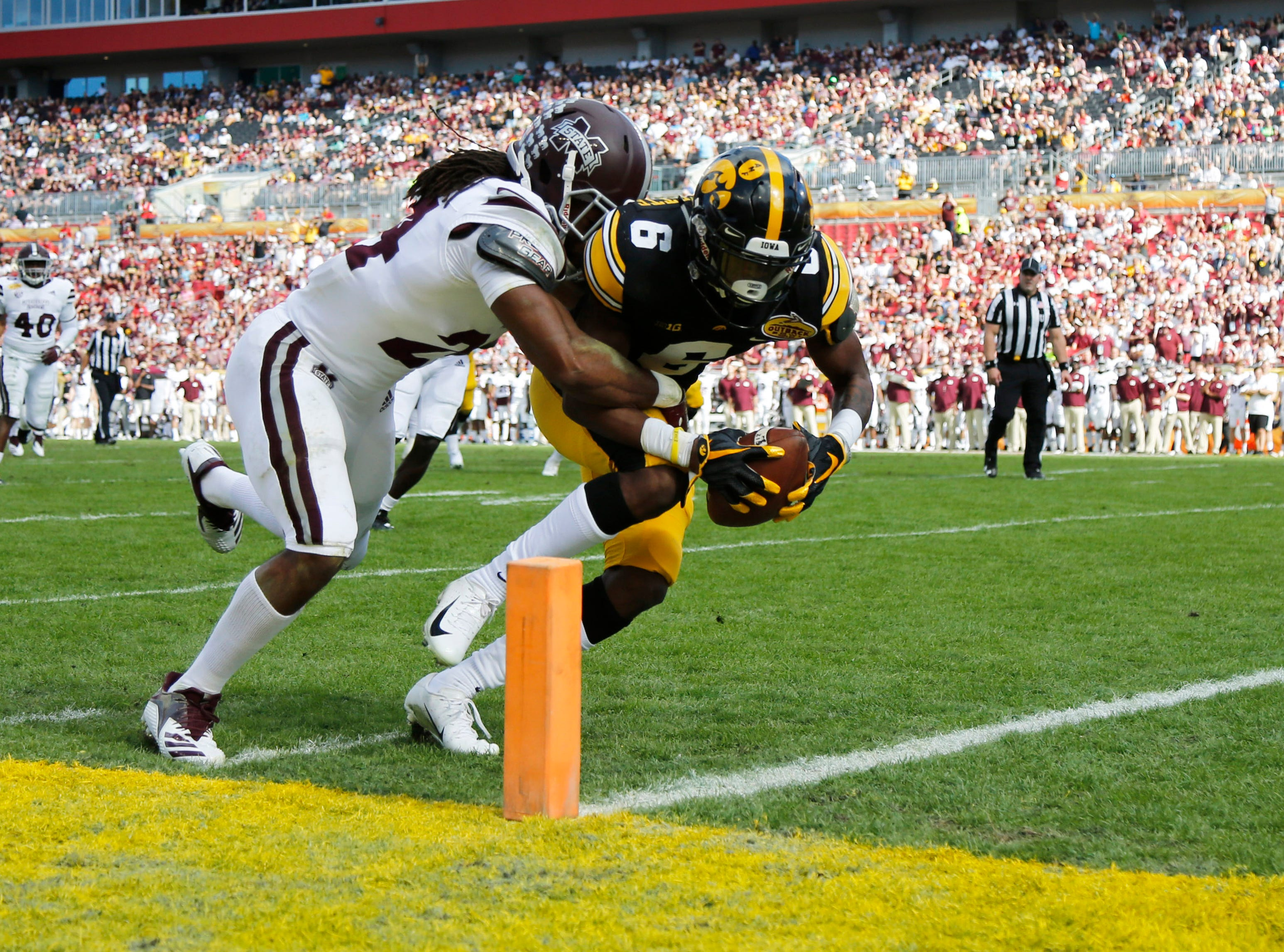 Iowa Hawkeyes wide receiver Ihmir Smith-Marsette (6) scores a touchdown past Mississippi State Bulldogs cornerback Chris Rayford (24) during the second quarter of the Outback Bowl.