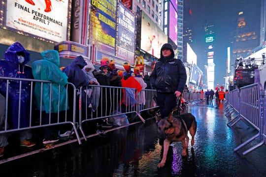 A New York City K-9 unit walks past revelers gathered on a rainy New Year's Eve.