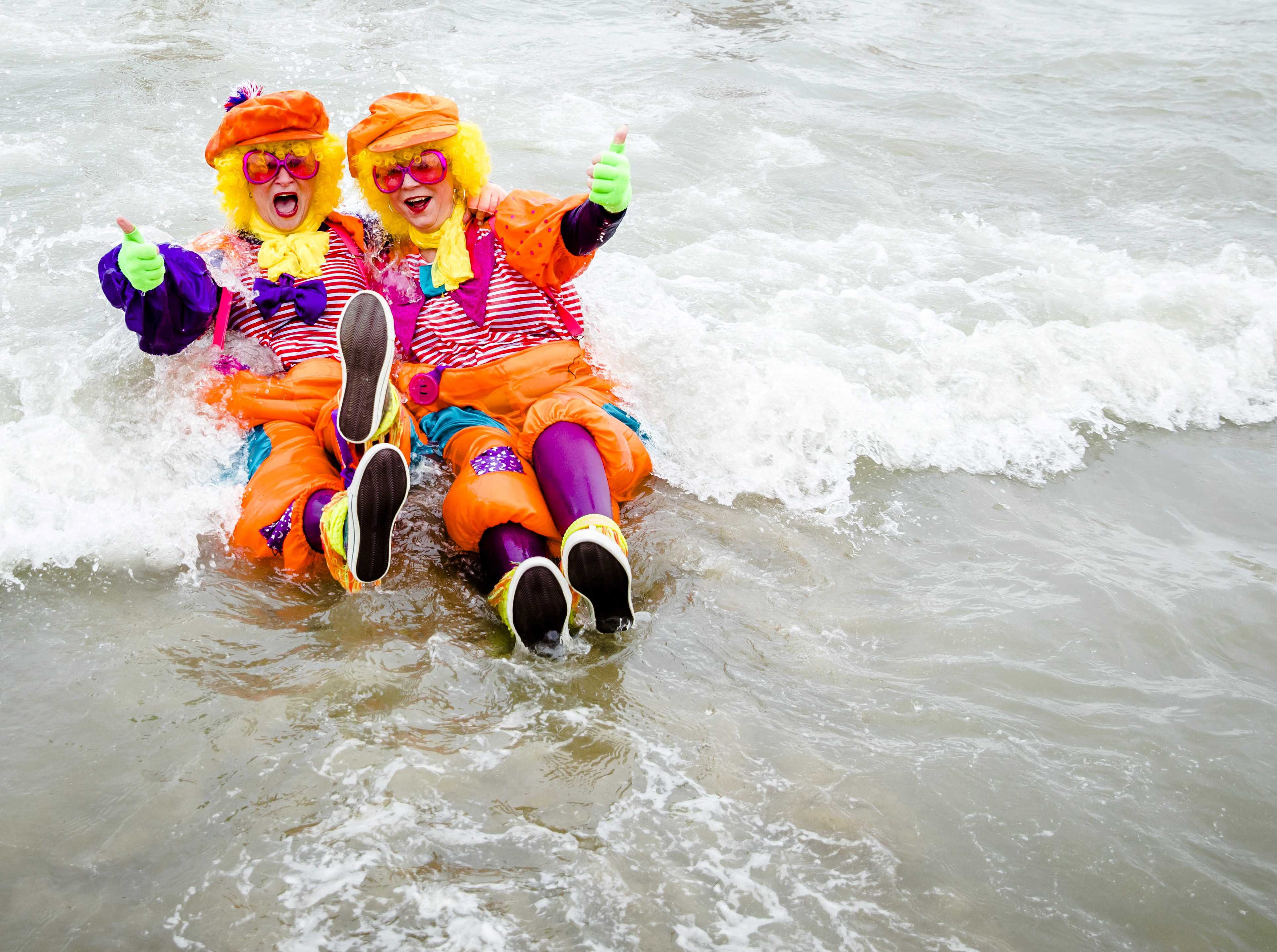 Costumed participants sit on the beach during the New Year Dive event in The North Sea, in Scheveningen, near The Hague, The Netherlands on Jan. 1, 2019.
