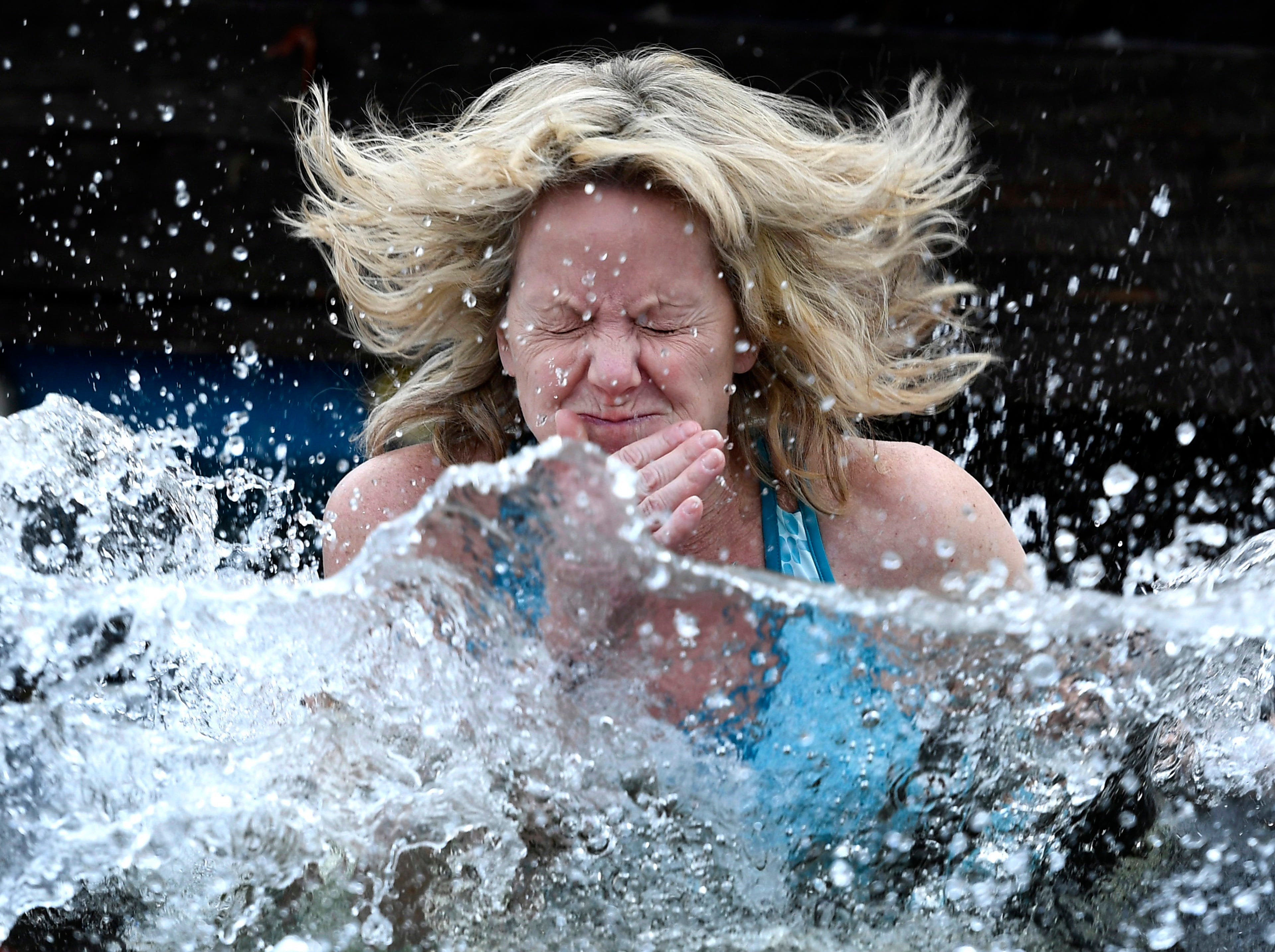 A reveler reacts as she jumps into the water during the Perth Polar Bear Plunge in Perth, Ontario, on New Year's Day, Tuesday, Jan. 1, 2019.