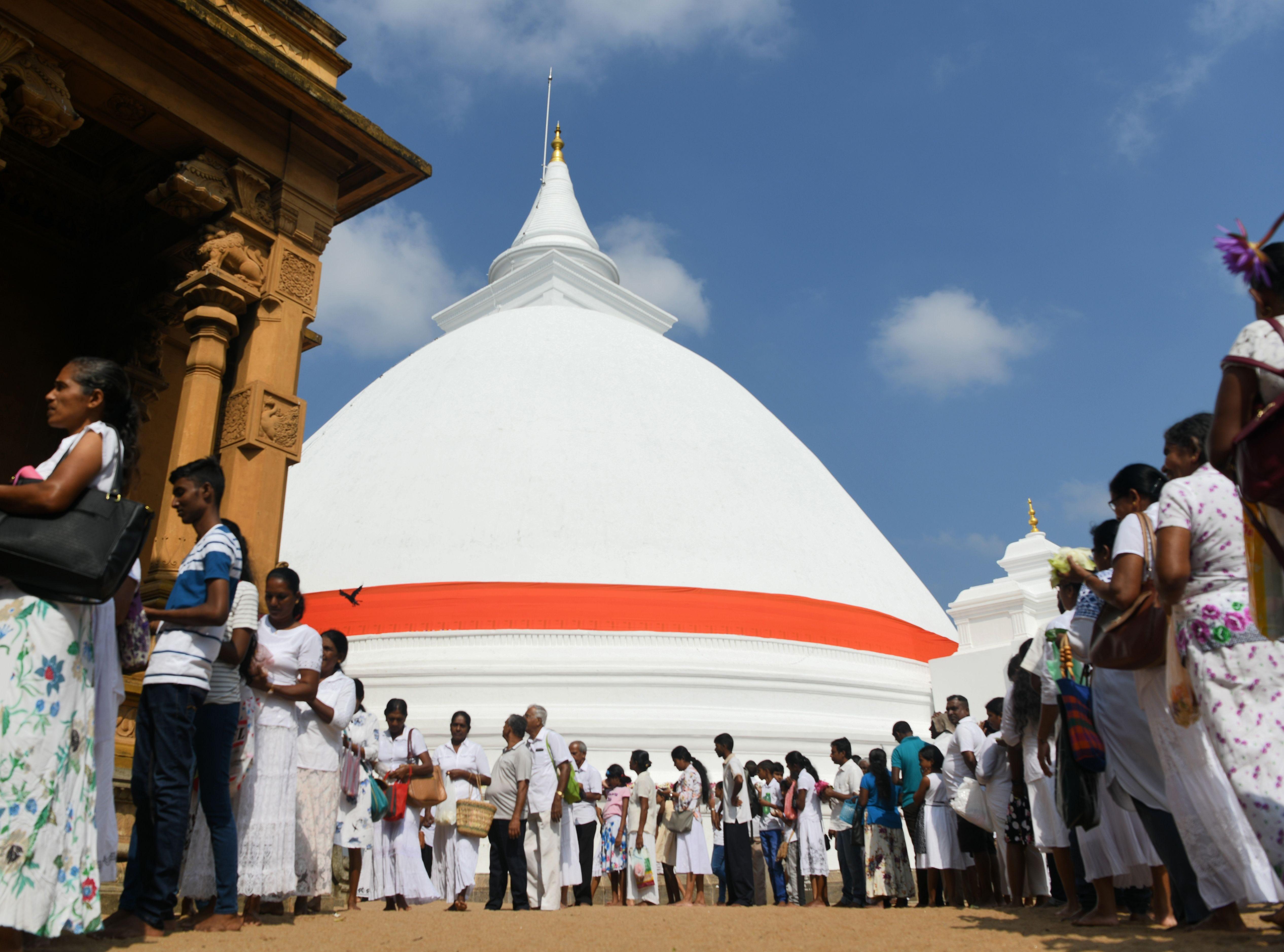 Sri Lankan Buddhist devotees line up to offer prayers to mark the new year at Kelaniya Raja Maha Vihara Buddhist temple in Colombo on Jan. 1, 2019.