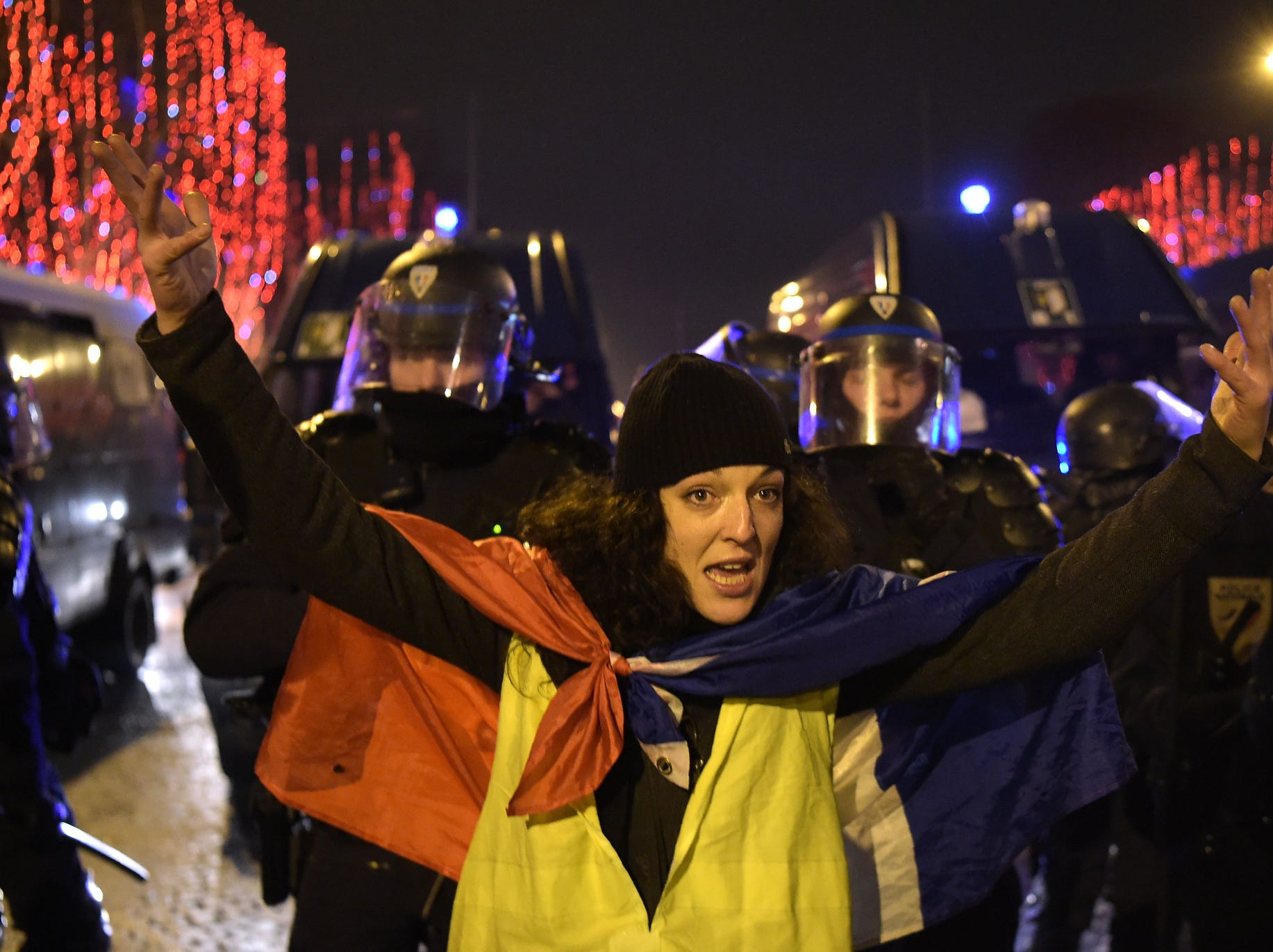 """A protestor wearing a """"Yellow vest"""" (gilet jaune) demonstrates in front of a row of French police on the Champs-Elysees in Paris during New Year's Celebrations. The yellow vests movement originally started as a protest about planned fuel hikes but has morphed into a mass protest against President's policies and top-down style of governing."""