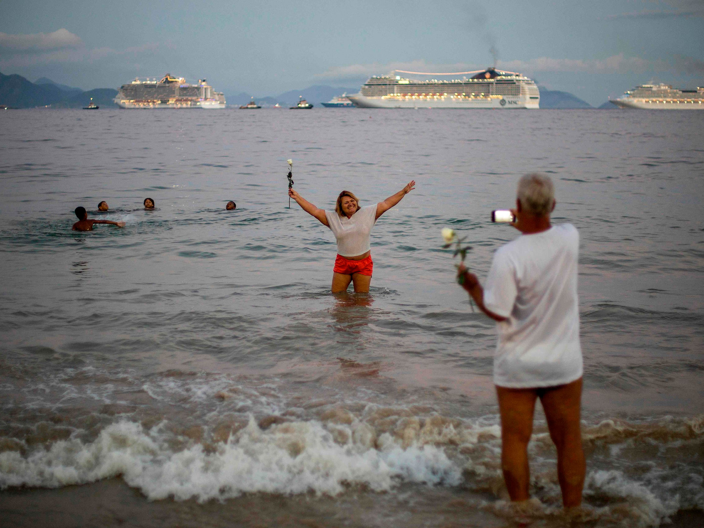Backdropped by cruises, a woman poses for pictures on the shore of Copacabana Beach in Rio de Janeiro, Brazil, on New Year's Eve.