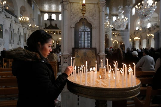 An Orthodox Christian worshipper lights candles during a Mass at the Greek Orthodox Mariamite Cathedral in Damascus, Syria, on Jan. 1, 2019.