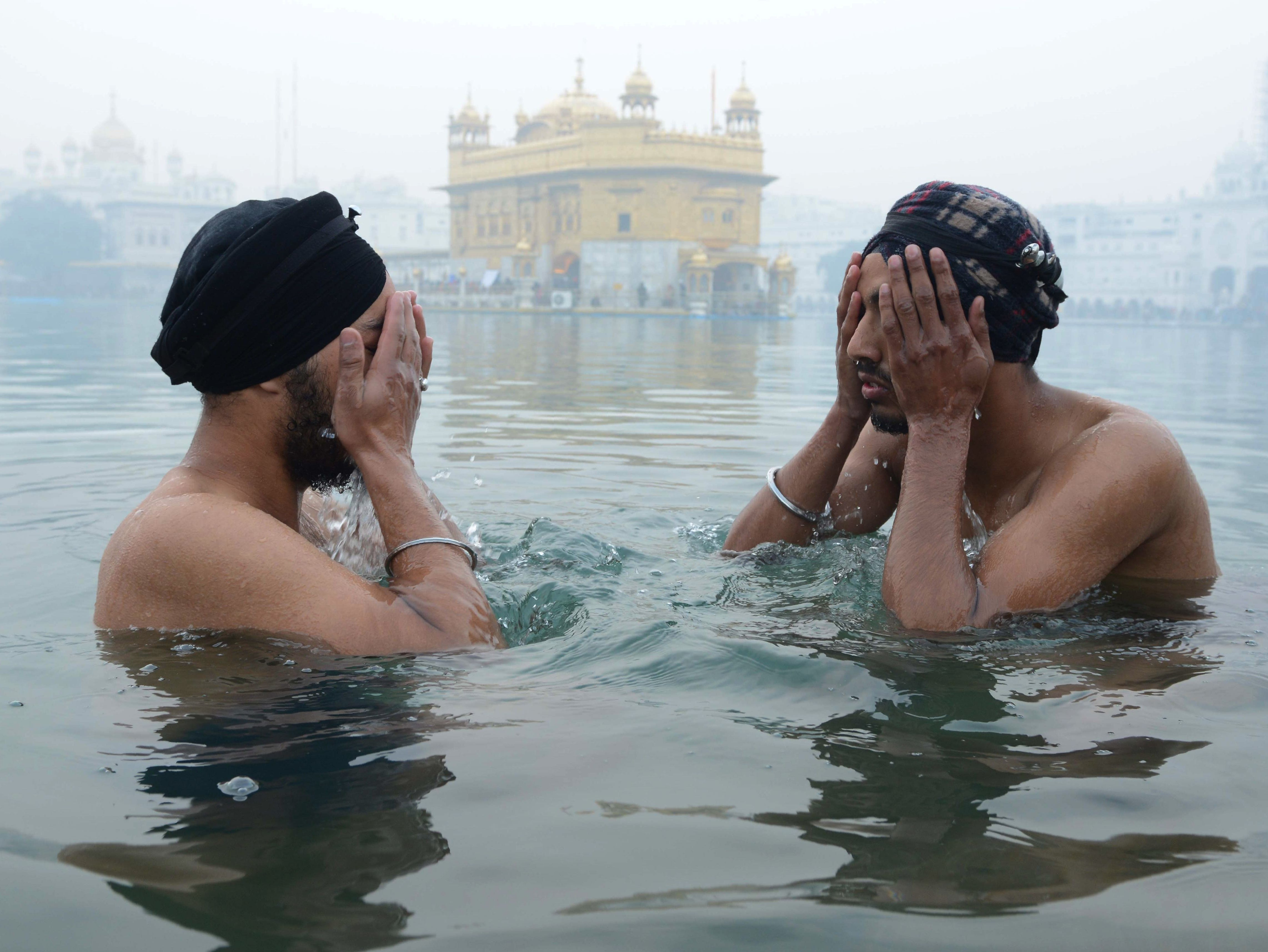 Indian Sikh devotees take a dip in the holy sarovar (water tank) in the early morning on New Year at the Sikh shrine Golden Temple in Amritsar on Jan. 1, 2019.